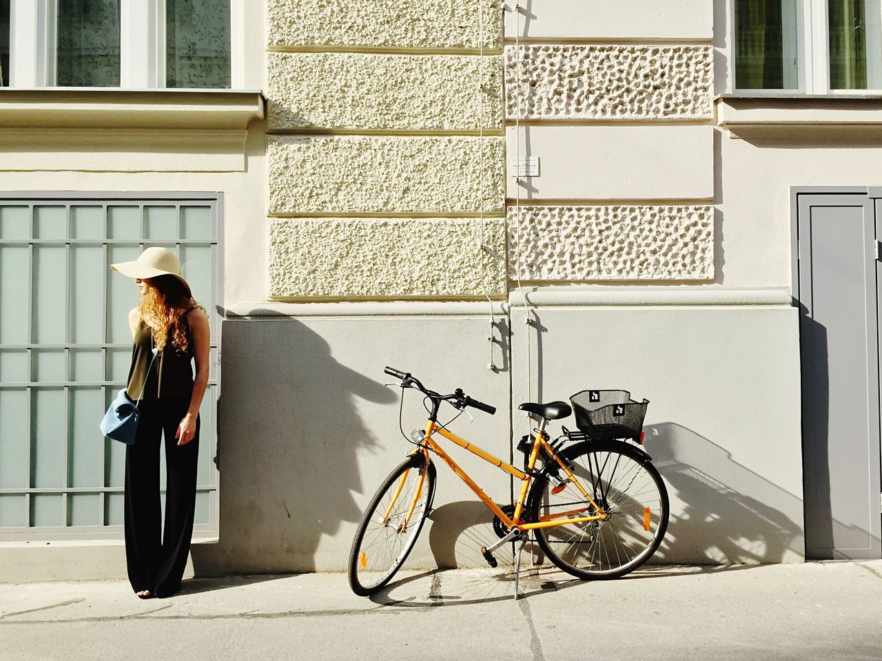 Young Woman Standing Besides Bicycle Against Building