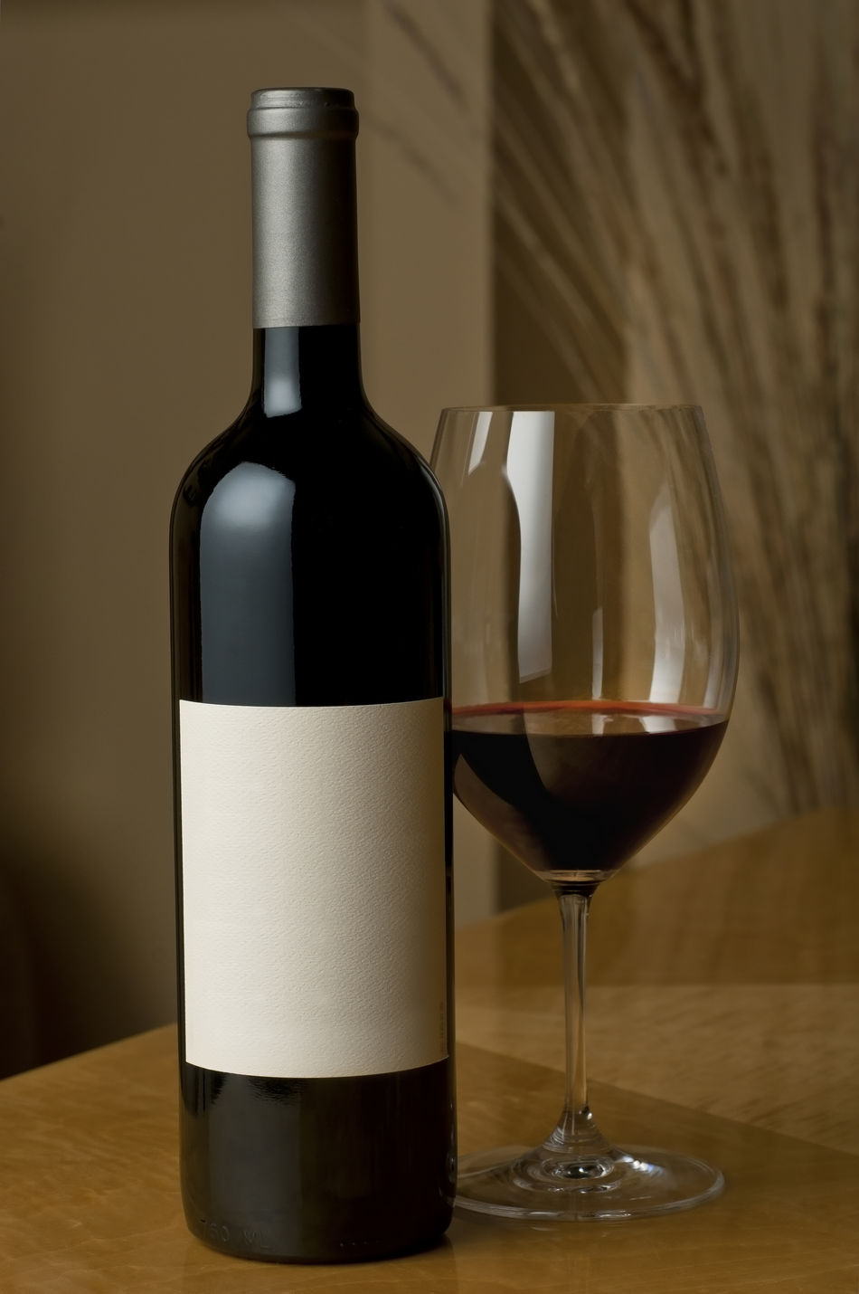 Wine bottle and glass Alcohol Beverage Blank Bottle Cabernet_sauvignon Close-up Focus On Foreground Glass In Indoors  Interior Label Merlot No People No Vintage One One Bottle Product Shot Still Life Table Vertical Composition Wine Bottle