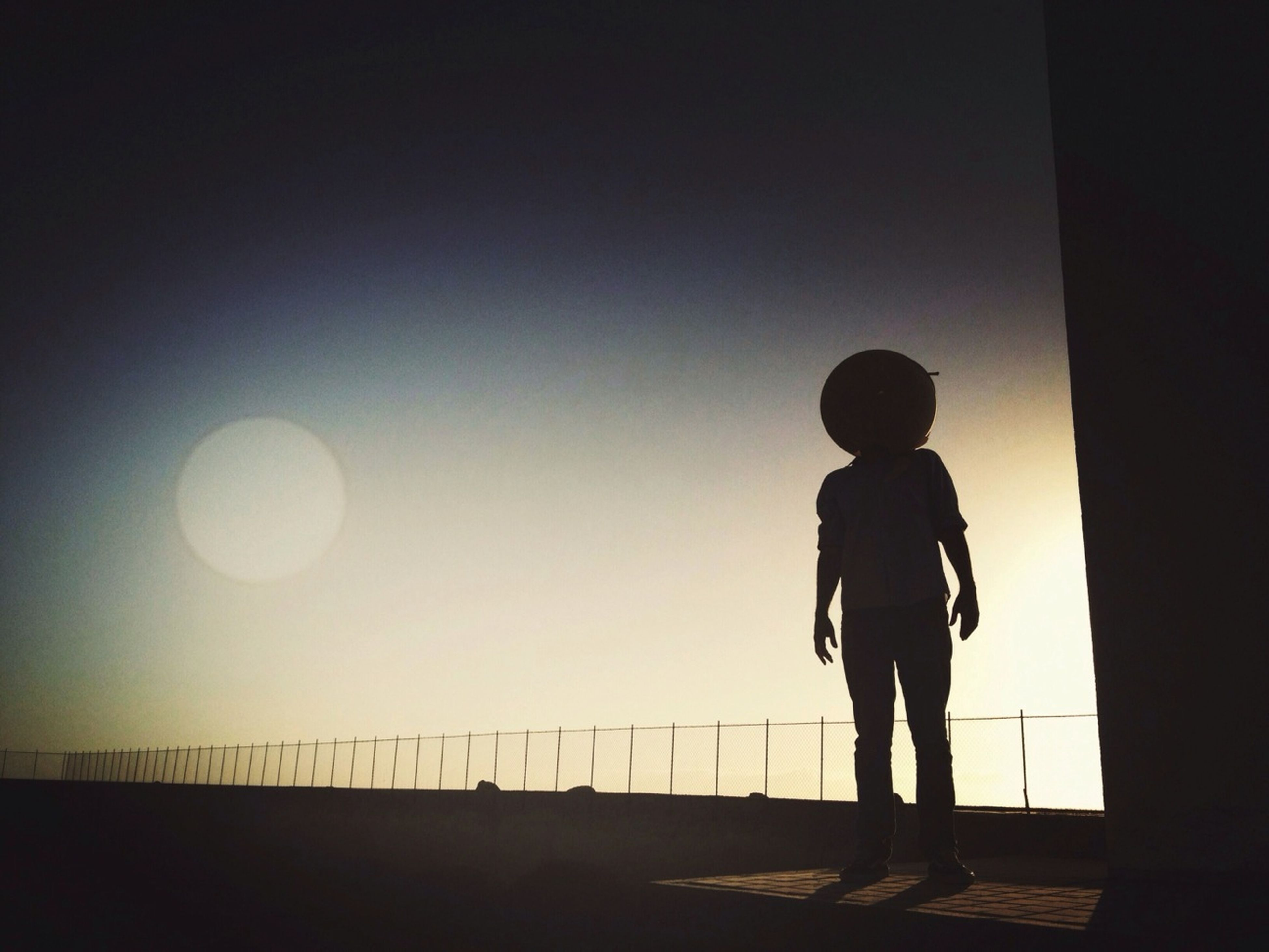 full length, standing, silhouette, rear view, lifestyles, copy space, leisure activity, childhood, boys, clear sky, men, casual clothing, walking, sunset, railing, indoors, three quarter length