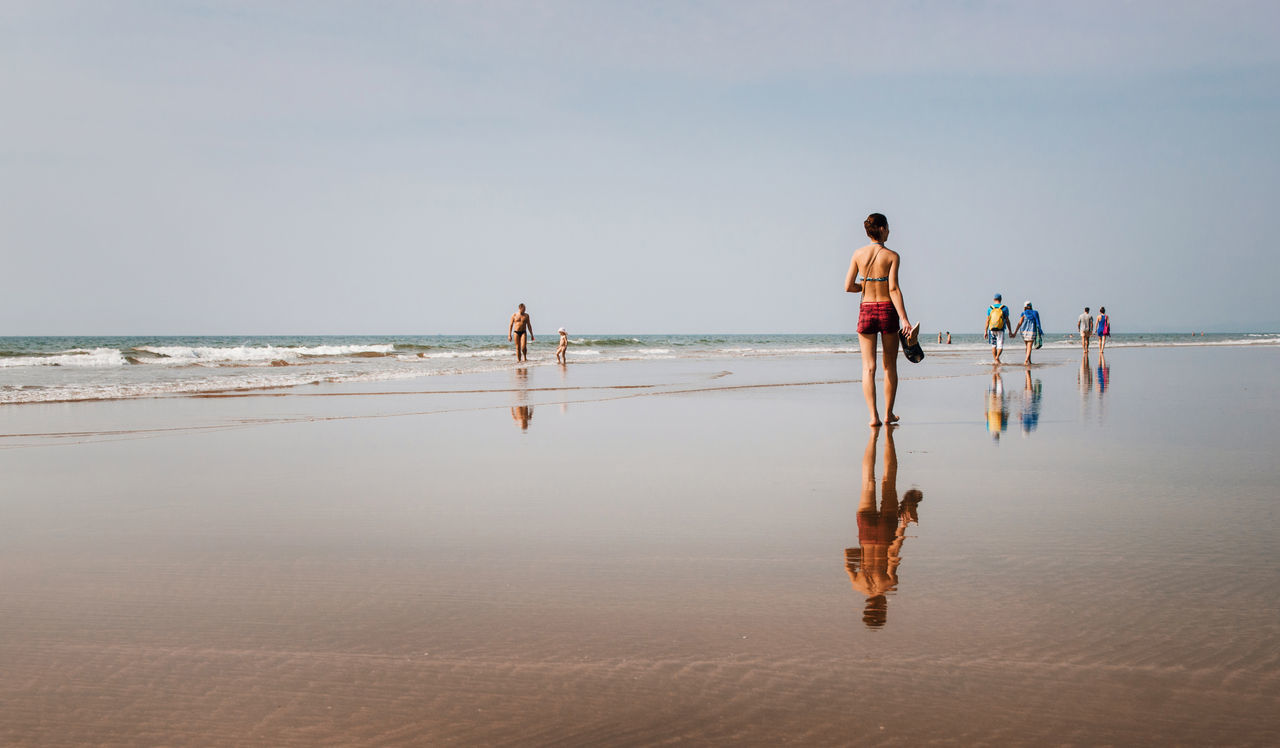 Young woman and people are walking and relaxing on the wide beach with mirror reflections, Ashvem, Goa, India Beach Horizon Over Water India Indian Leisure Activity Long Goodbye Mirror Outdoors Reflection Reflections Reflections In The Water Sand Sea Sky Vacations Walking