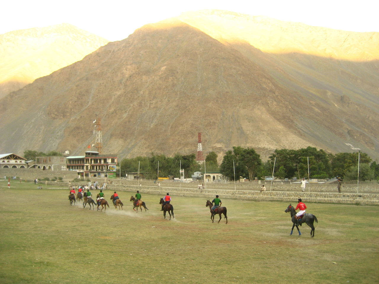 horse, mountain, domestic animals, horseback riding, mammal, competition, sport, horse racing, real people, field, men, jockey, riding, mountain range, competitive sport, landscape, day, nature, large group of people, outdoors, sports race, sports track, grass, adult, people