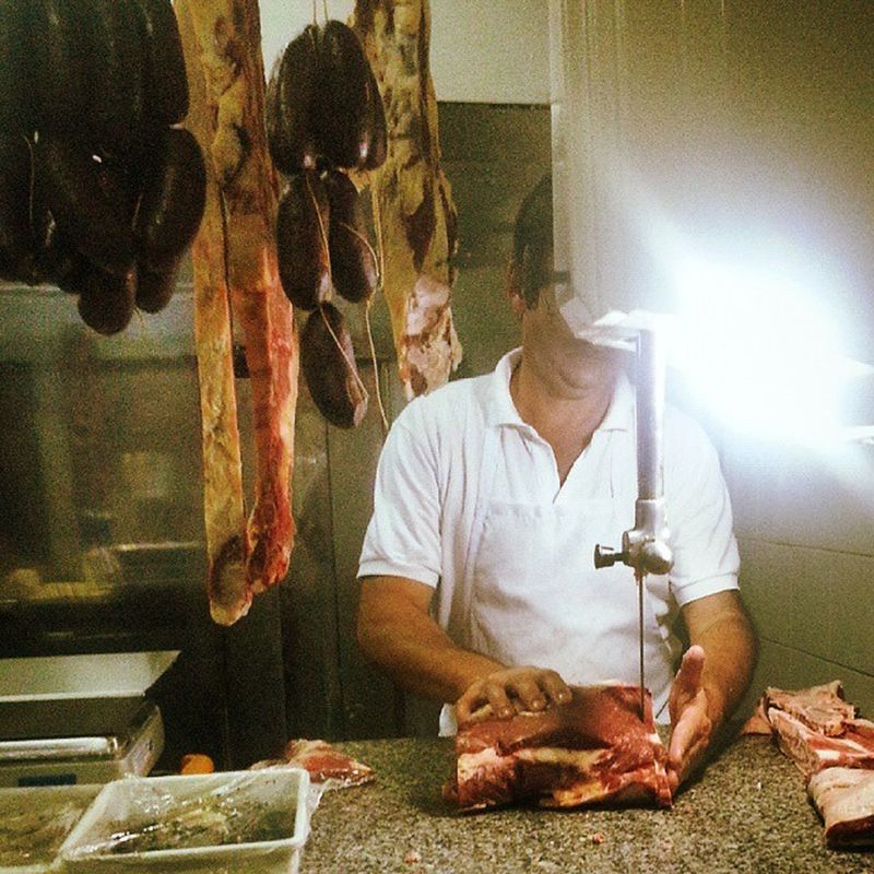 Meat at butcher cut to order for an asado. The best cuts are hanging longest to the left, Argentina will not export them as it contains rib bones and the marrow doesn't travel well. Tasty blood and date sausages displayed as well, the flies on them are free of charge. Carne Asado