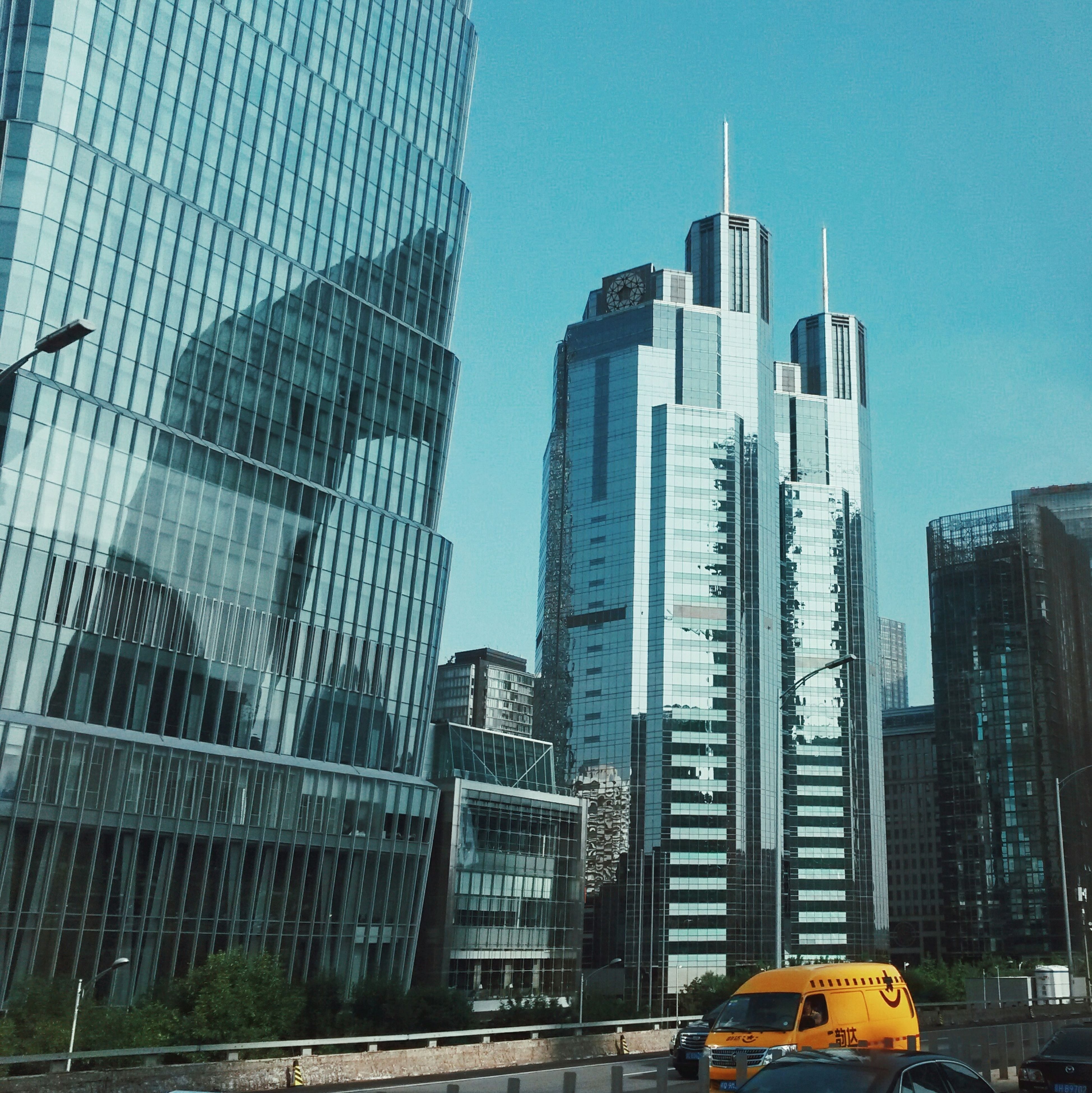 skyscraper, architecture, building exterior, built structure, city, tall - high, modern, tower, tall, development, day, transportation, car, low angle view, outdoors, land vehicle, travel destinations, no people, sky, cityscape, urban skyline, office park