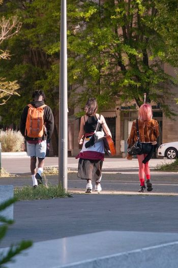 Walking People Young Adult Day Casual Clothing Road Men Women Friendship Outdoors Trio Three Style Guitar Guitarist Friends Streetphotography Street Fashion Fashion Colors Stockings Red Stockings Hairstyle Haircut Coloured Hair