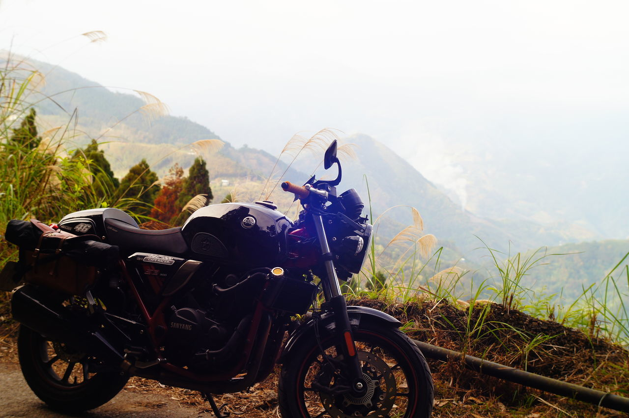 mountain, transportation, mode of transport, nature, land vehicle, day, mountain range, beauty in nature, landscape, no people, outdoors, motorcycle, sky