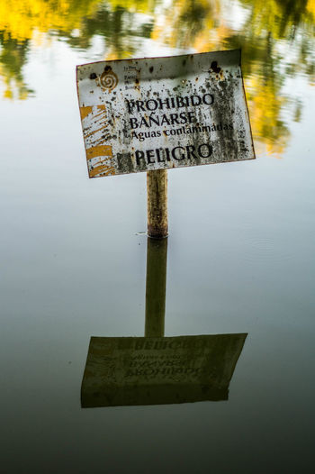 Information Information Sign No People Outdoors Reflection Sign Text Warning Sign Water Water Reflections