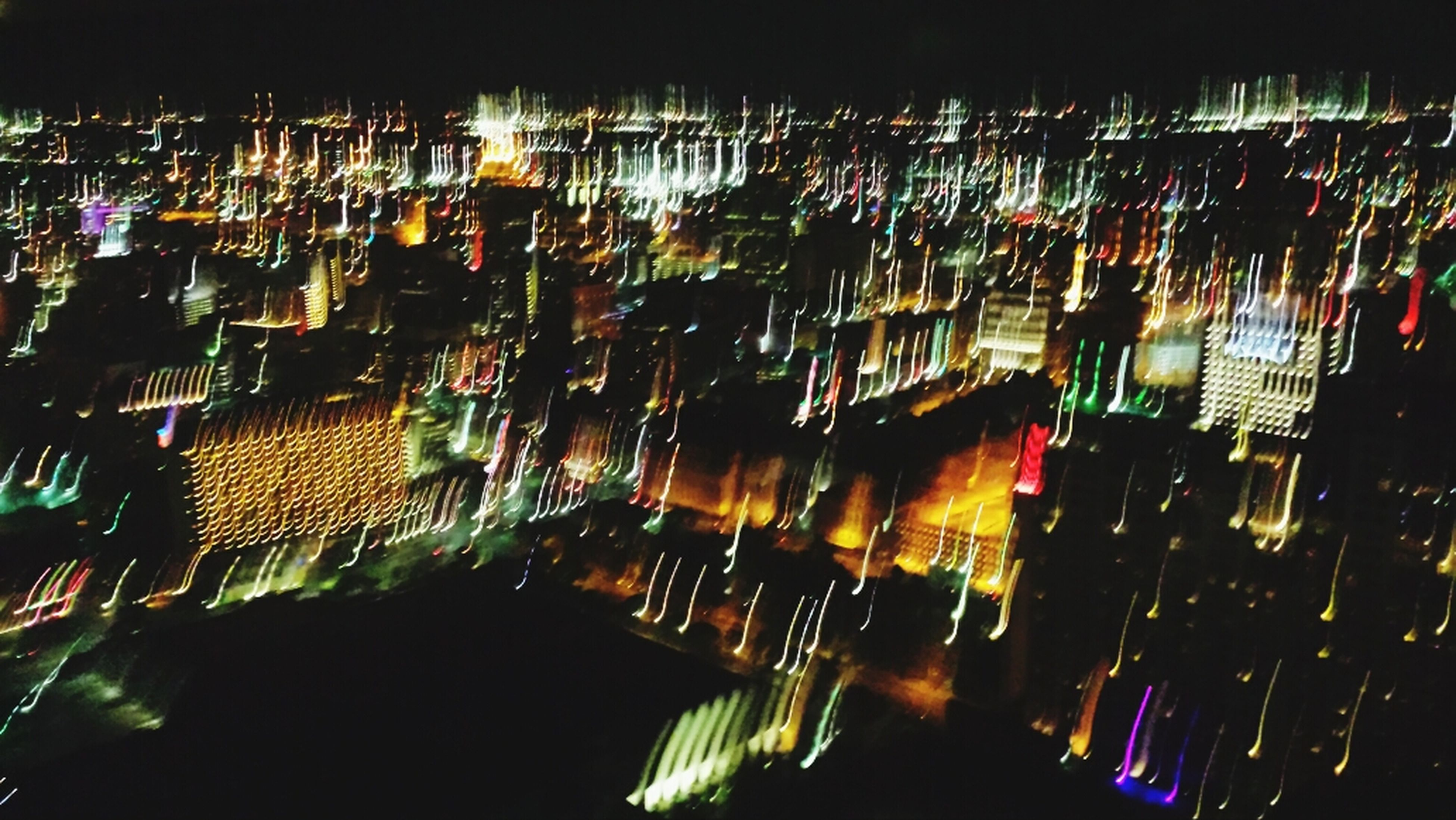 illuminated, night, building exterior, city, architecture, built structure, cityscape, high angle view, skyscraper, crowded, modern, city life, lighting equipment, residential building, light - natural phenomenon, office building, no people, outdoors, residential structure, abundance