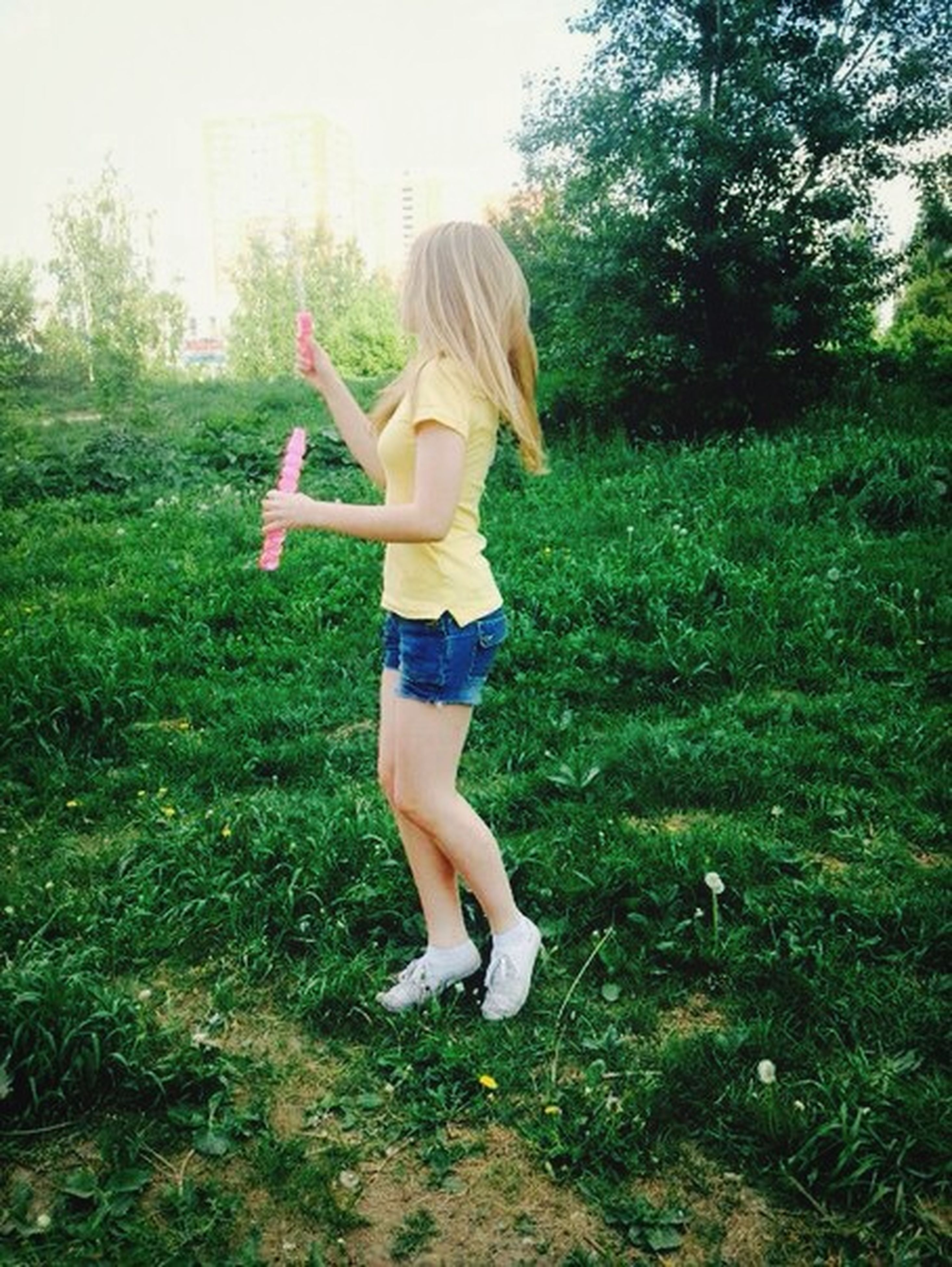 full length, person, grass, casual clothing, lifestyles, young adult, leisure activity, childhood, young women, elementary age, field, girls, standing, fun, grassy, arms outstretched, happiness, three quarter length
