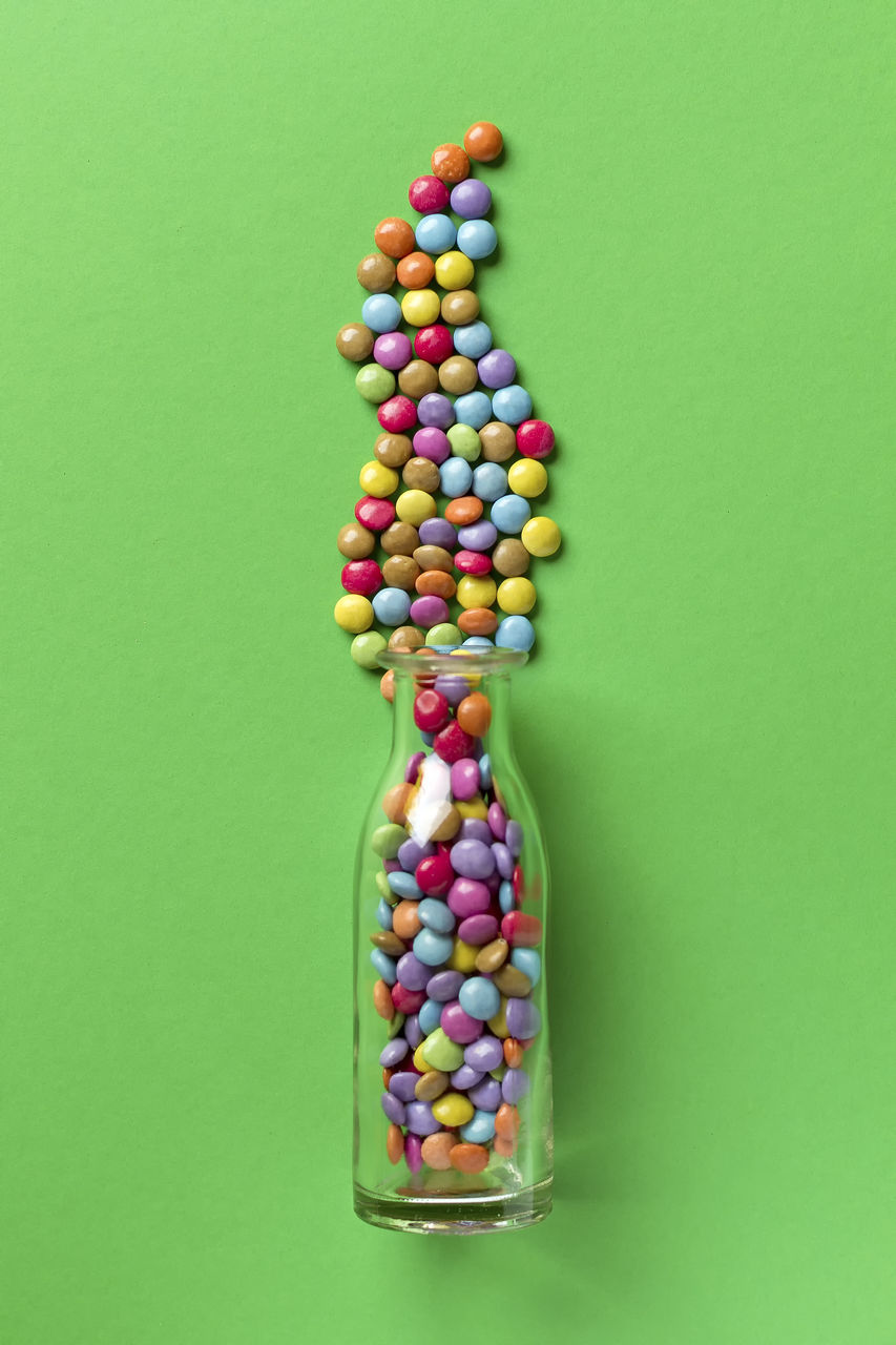 Close-Up Of Candies Spilling From Bottle Over Green Background