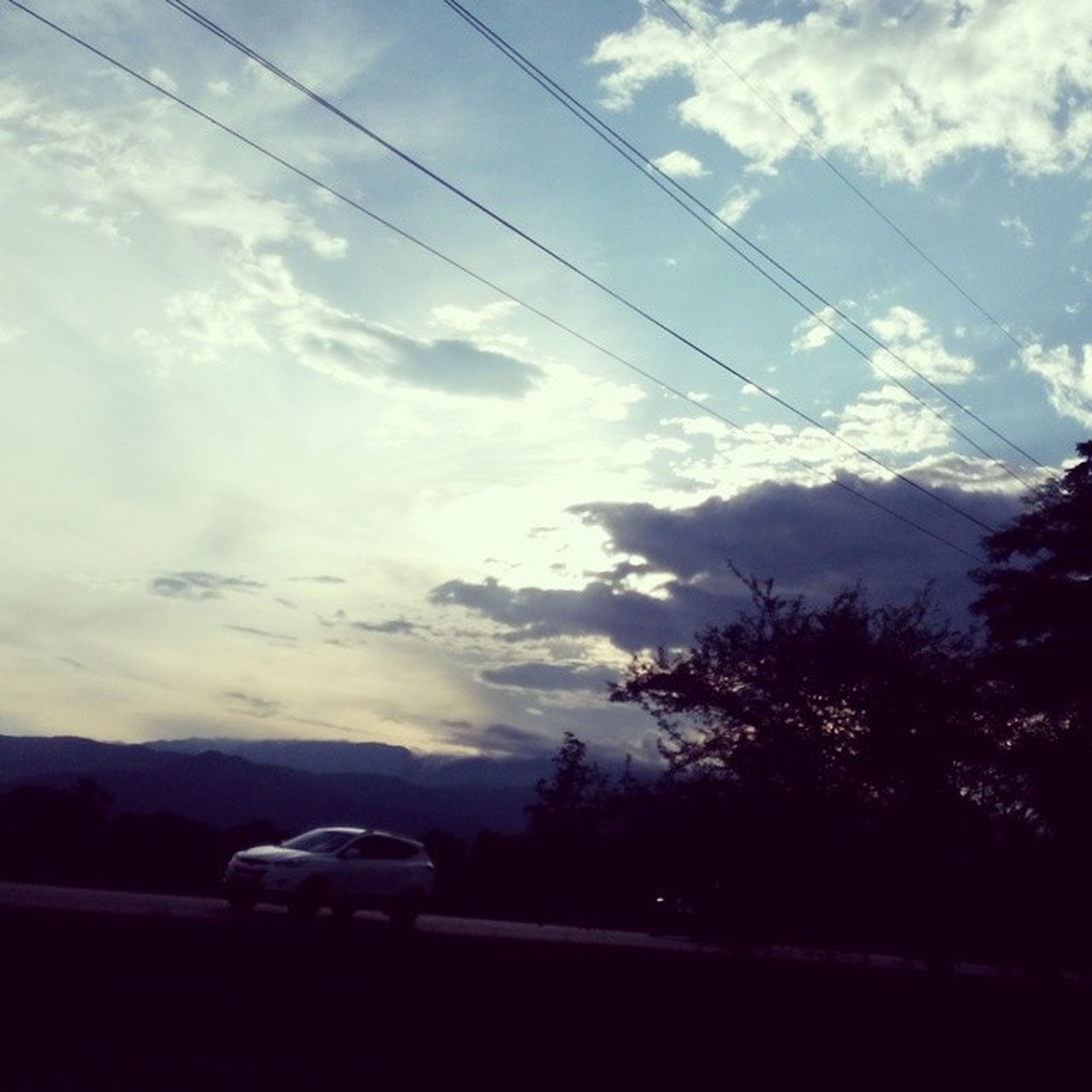 transportation, sky, tree, road, land vehicle, mode of transport, car, cloud - sky, silhouette, cloud, cloudy, tranquil scene, mountain, scenics, tranquility, nature, on the move, travel, beauty in nature, landscape