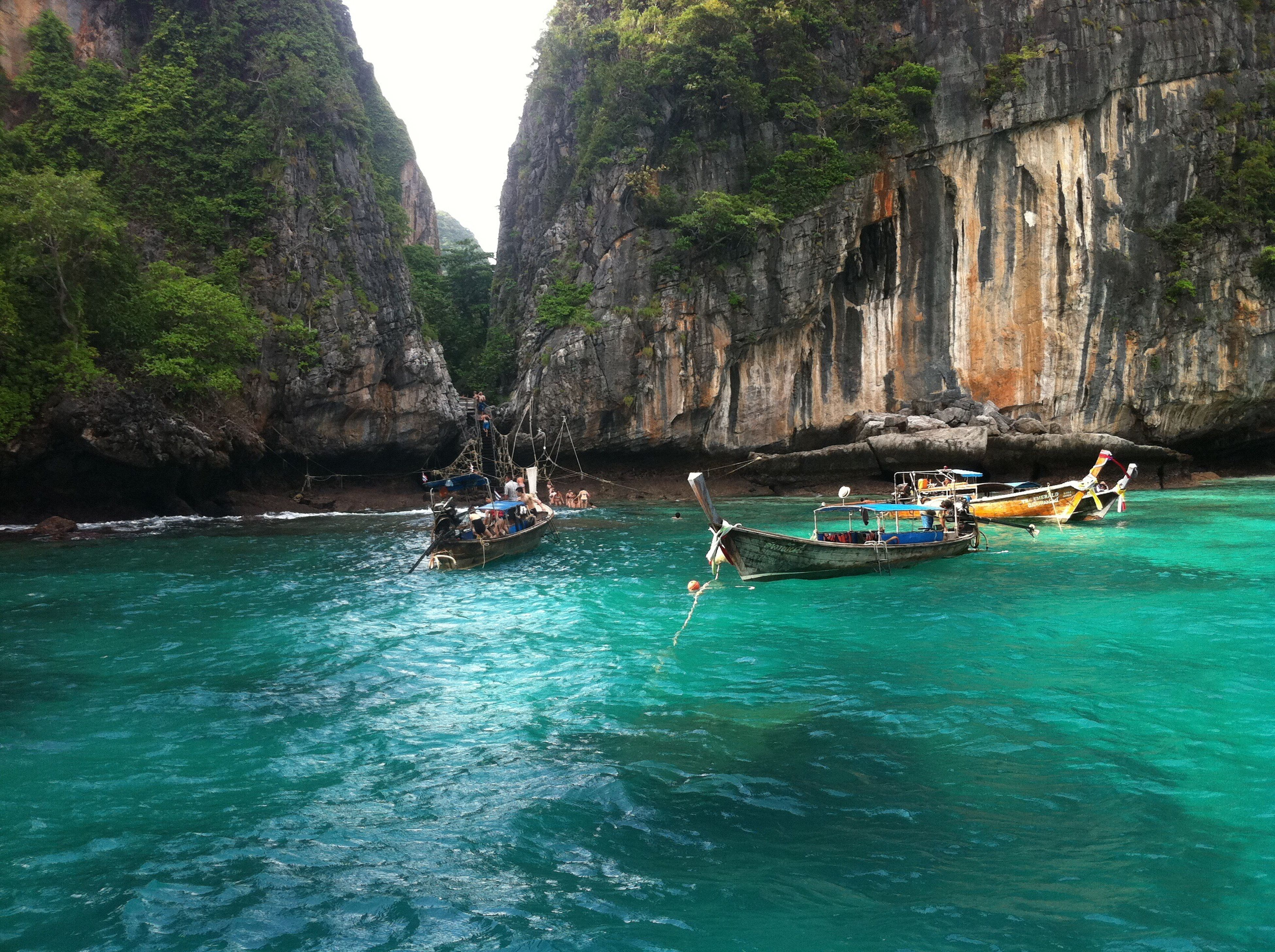 water, nautical vessel, boat, waterfront, mode of transport, tree, mountain, tranquil scene, tranquility, beauty in nature, scenics, nature, rock formation, blue, rippled, idyllic, vacations, sailing, day, outdoors, turquoise colored, tourism, travel destinations, sky, non-urban scene, non urban scene, remote
