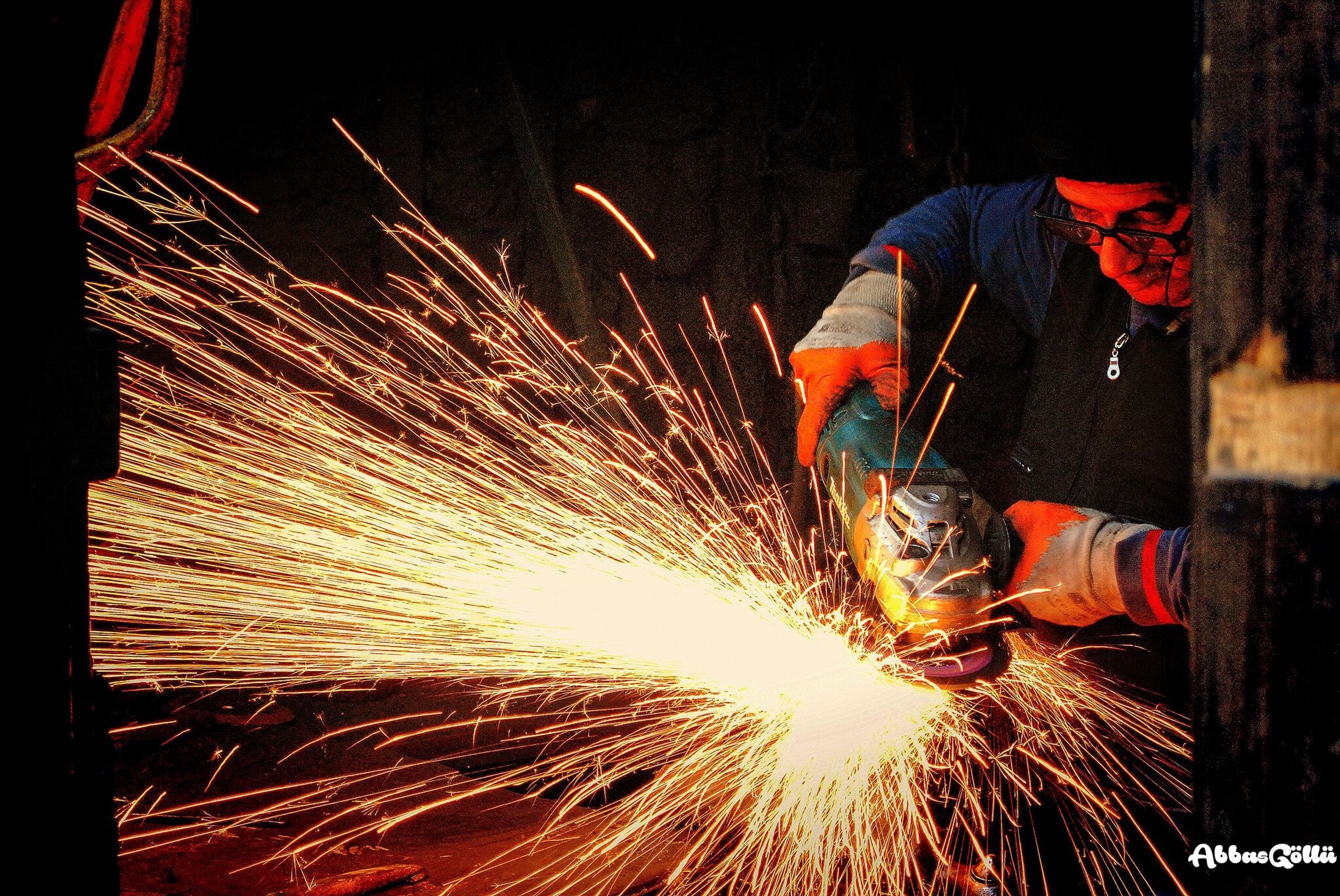 working, one person, industry, occupation, one man only, only men, adults only, indoors, illuminated, heat - temperature, skill, midsection, people, motion, men, grinder, metal industry, steel mill, speed, manual worker, workshop, adult, night, welder