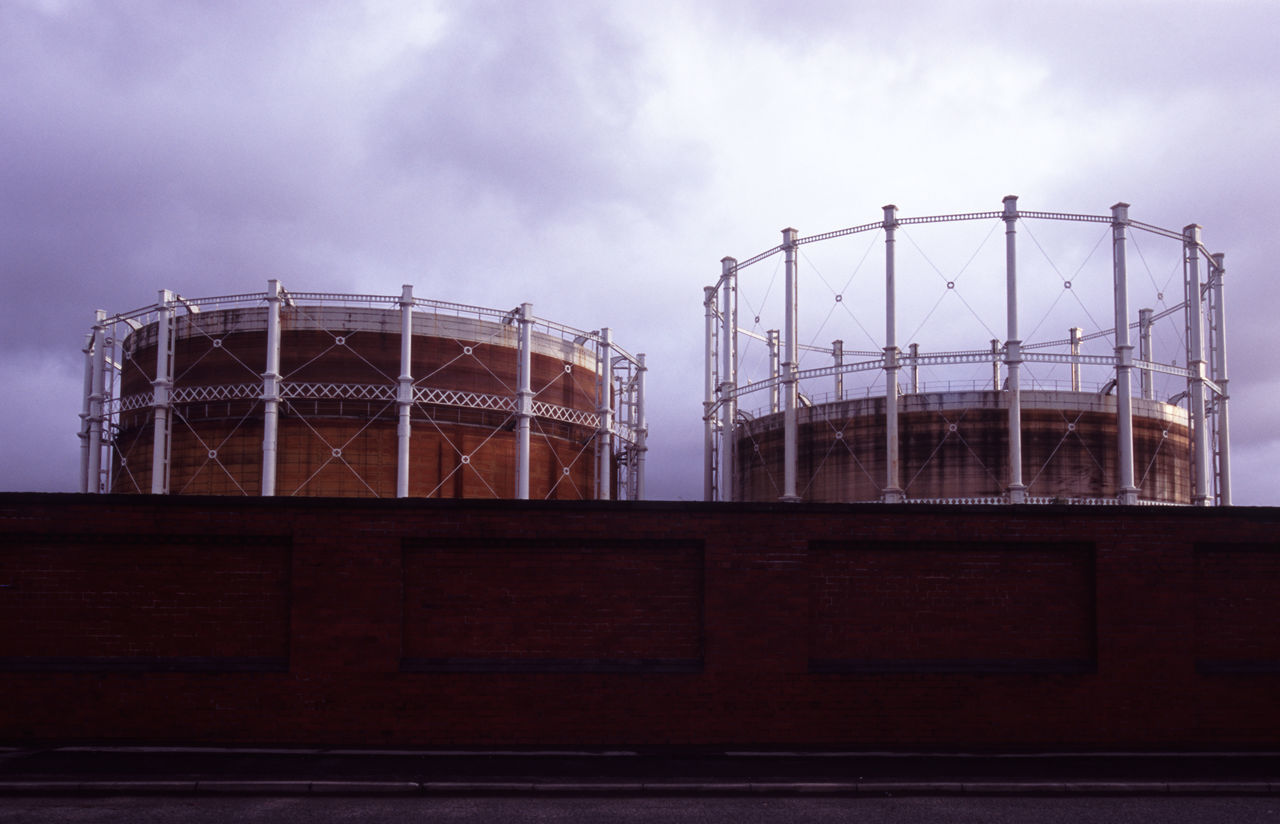 rusting gas storage towers in salford, manchester Brick Wall Built Structure Clouds Construction Engineering Gas Gas-holder Gasometer Gasworks Machester Metal Salford