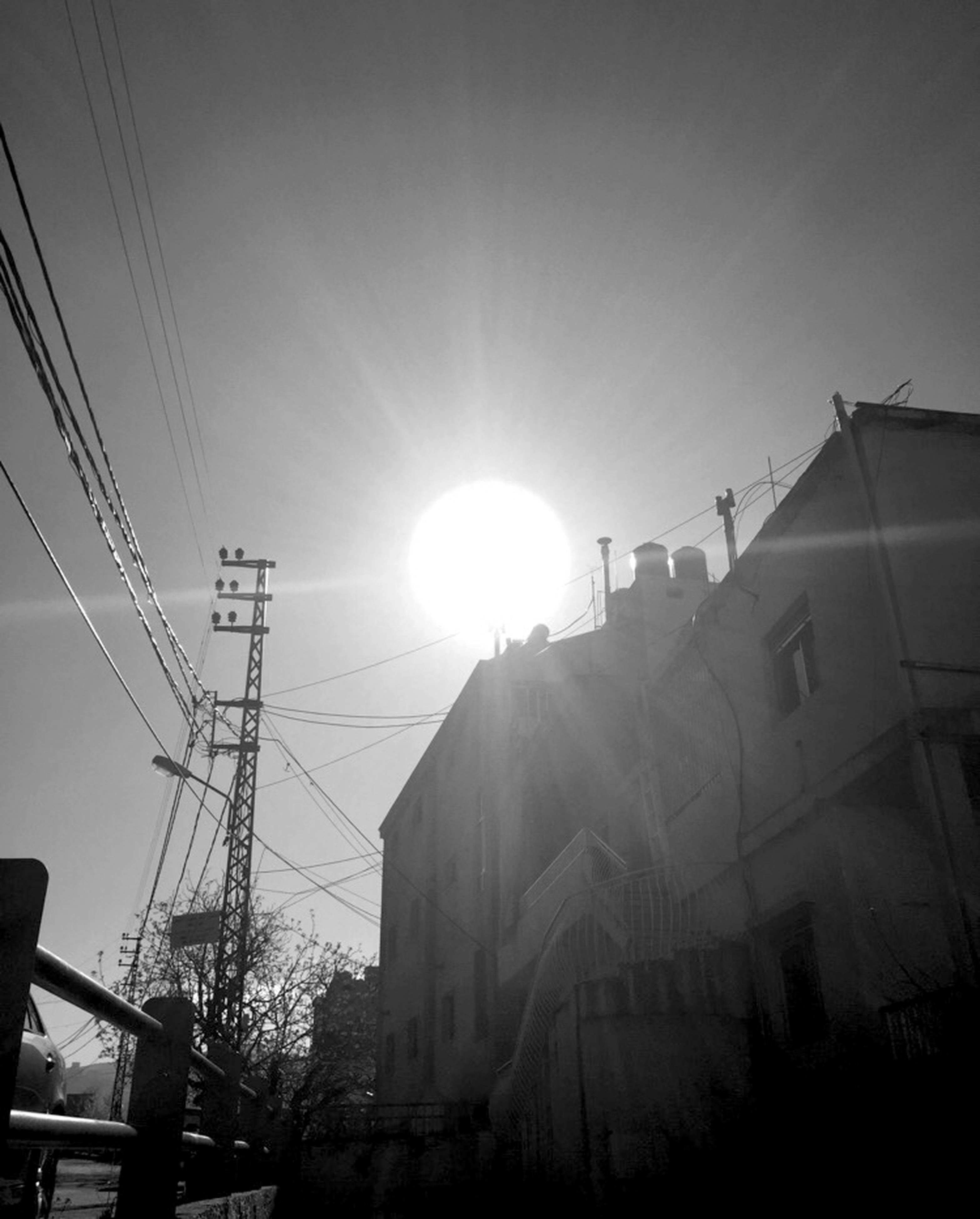 architecture, built structure, building exterior, sun, power line, low angle view, electricity pylon, sunbeam, sunlight, cable, electricity, lens flare, connection, sky, power supply, silhouette, city, building, fuel and power generation, power cable