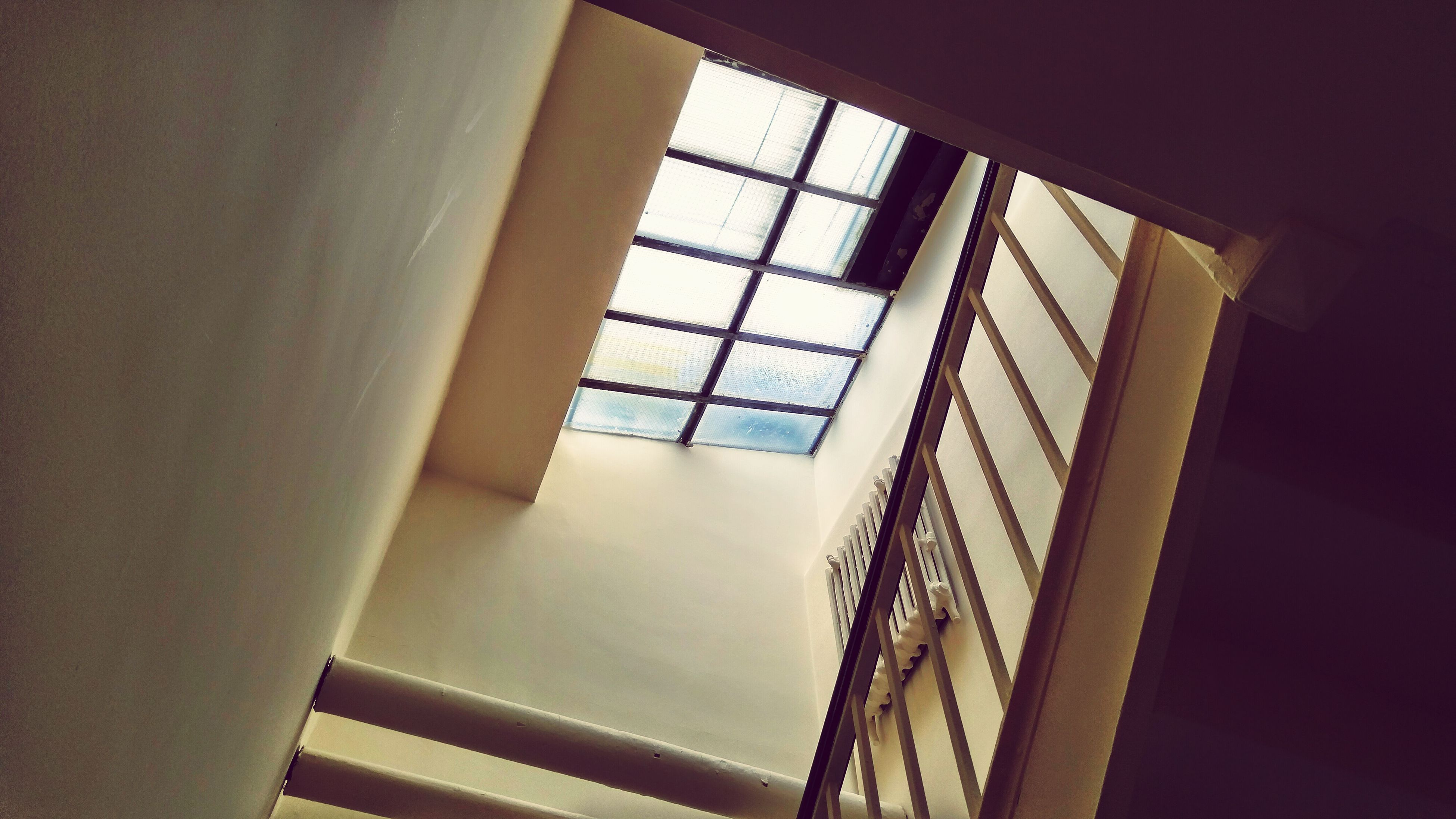 indoors, architecture, built structure, low angle view, staircase, railing, steps and staircases, steps, modern, building, window, ceiling, building exterior, glass - material, no people, directly below, pattern, day, skylight, sunlight