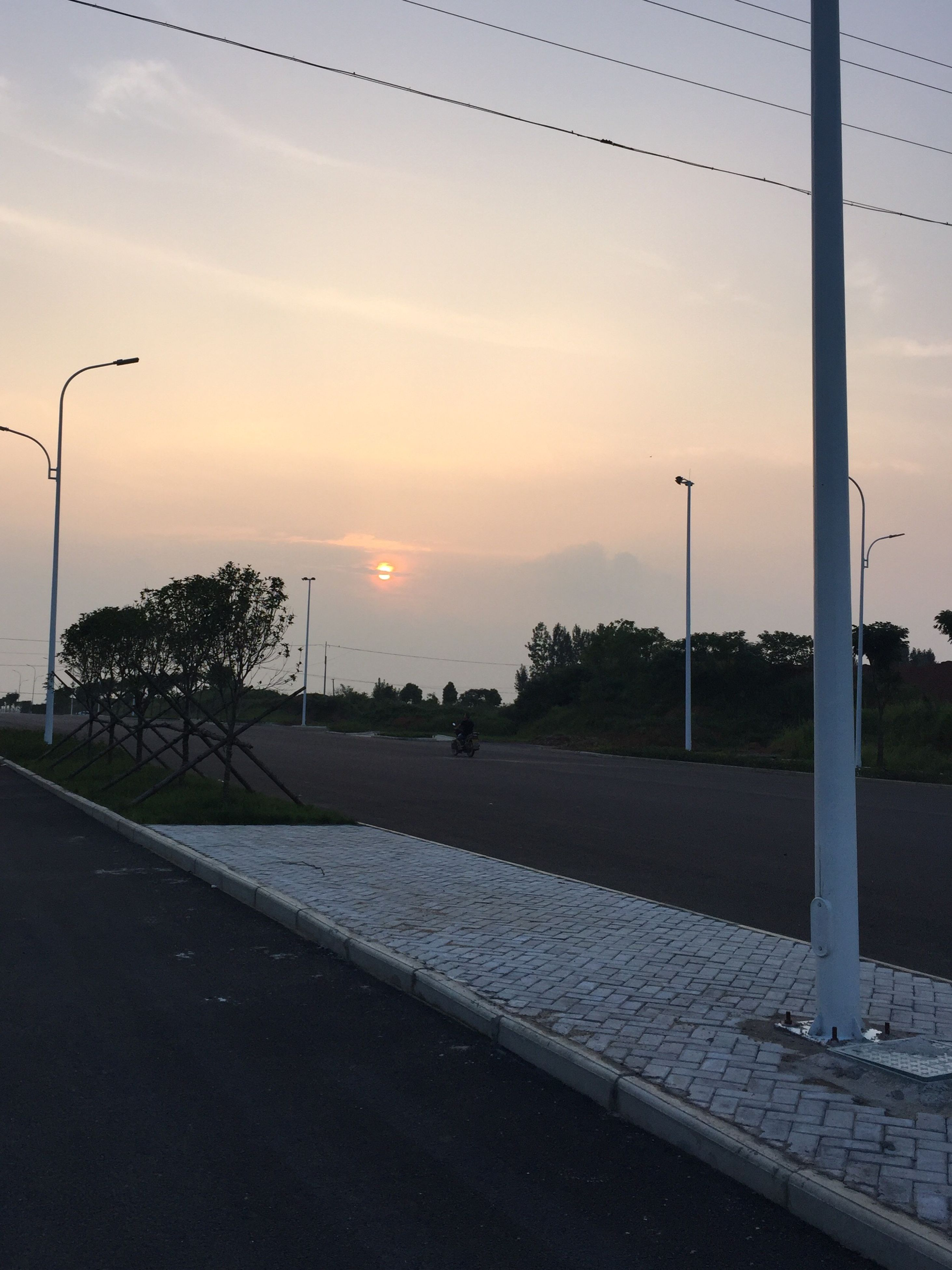 street light, sunset, tree, sky, road, the way forward, lighting equipment, cloud - sky, empty, tranquility, pole, outdoors, nature, tranquil scene, no people, cloud, scenics, orange color, beauty in nature, diminishing perspective, sun, landscape, idyllic