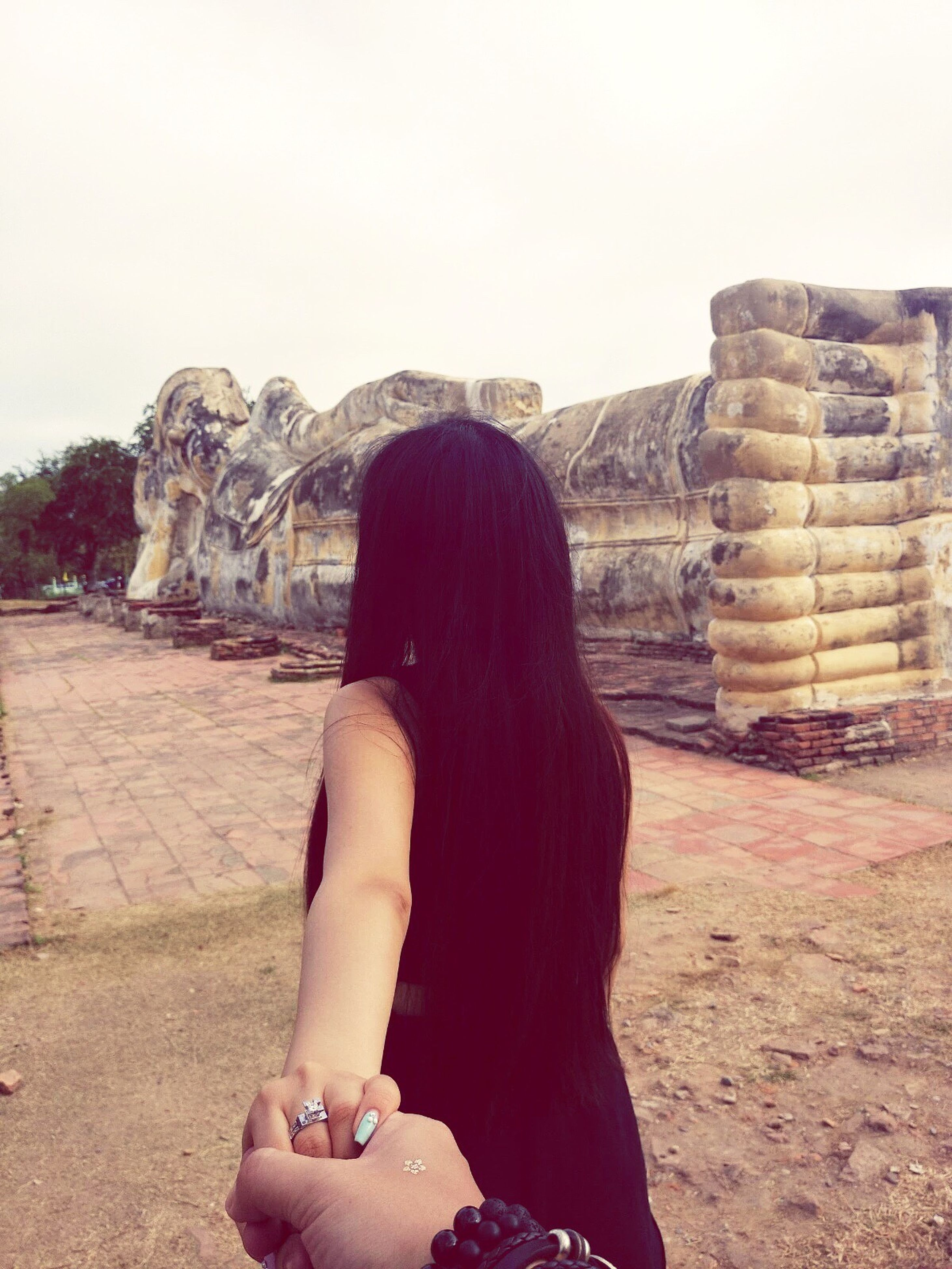 lifestyles, leisure activity, person, rear view, young adult, young women, casual clothing, clear sky, standing, built structure, full length, architecture, sitting, long hair, history, old ruin, day, building exterior
