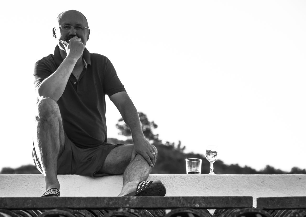 Low Angle Portrait Of Mid Adult Man Having Drink While Sitting On Building Terrace Against Clear Sky