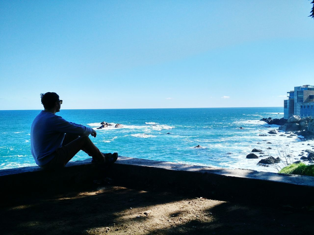 sea, horizon over water, clear sky, blue, one person, water, real people, sitting, nature, beach, beauty in nature, full length, scenics, lifestyles, sky, men, day, outdoors, people