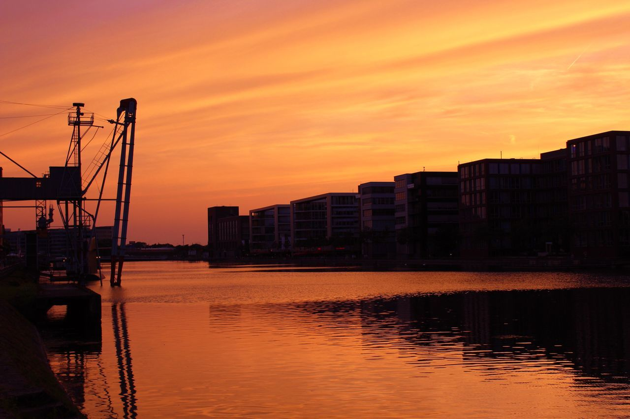 sunset, orange color, reflection, water, silhouette, sky, waterfront, architecture, no people, built structure, beauty in nature, nature, sun, scenics, building exterior, outdoors