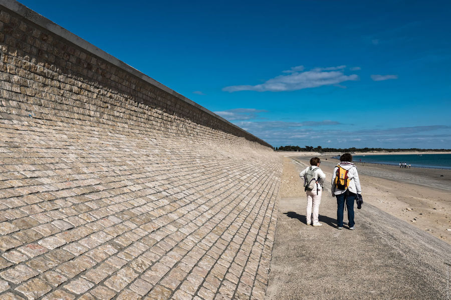 Adult Adults Only Breakwater Day Full Length Outdoors Real People Sea And Sky Sea Wall Seaside Sky Standing Sunlight Togetherness Walking