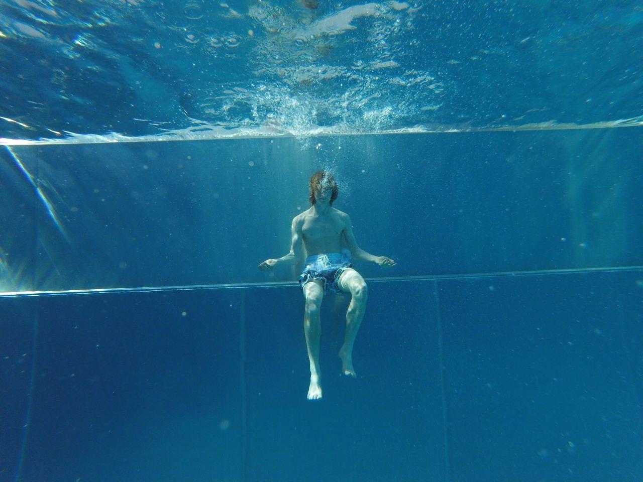 Shirtless Man Swimming Underwater