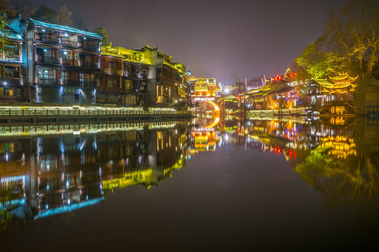 Reflection Of Illuminated Houses On River At Night