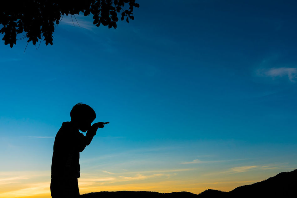 Beauty In Nature Boy Day Direction Finger Human Hand Kid Leisure Activity Lifestyles Men Mobile Phone Nature One Person Outdoors People Photographing Point Real People Silhouette Sky Standing Sunset Tree