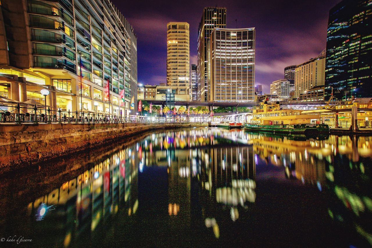 architecture, building exterior, night, illuminated, built structure, city, reflection, waterfront, skyscraper, water, modern, city life, no people, outdoors, travel destinations, cityscape, urban skyline, sky