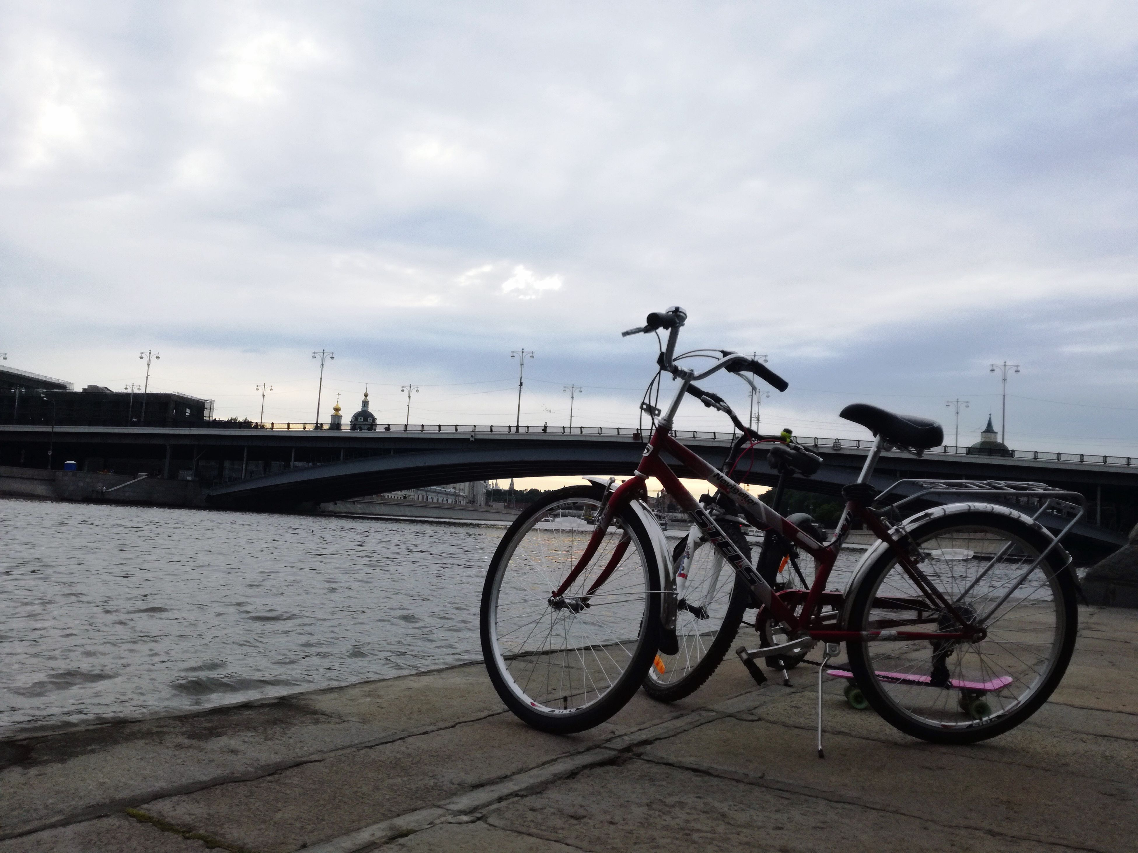 bicycle, transportation, mode of transport, sky, water, land vehicle, outdoors, no people, bridge - man made structure, built structure, sea, cloud - sky, city, day, architecture, nature