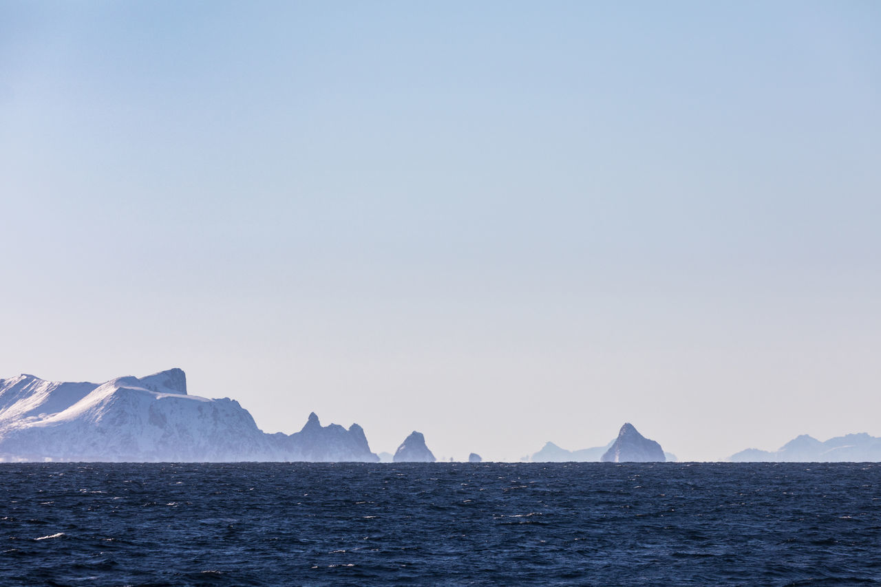 Skyline with rocky islands seen from a boat in the Norwegian Sea Arctic Beauty In Nature Blue Clear Sky Cold Temperature Copy Space Island Lofoten And Vesteral Islands Mountain Mountain Range Nature Non-urban Scene Norwegian Sea Outdoors Polar Climate Remote Rippled Rough Scenics Sea Snow Snowcapped Mountain Urban Skyline Waterfront Winter The Great Outdoors - 2017 EyeEm Awards