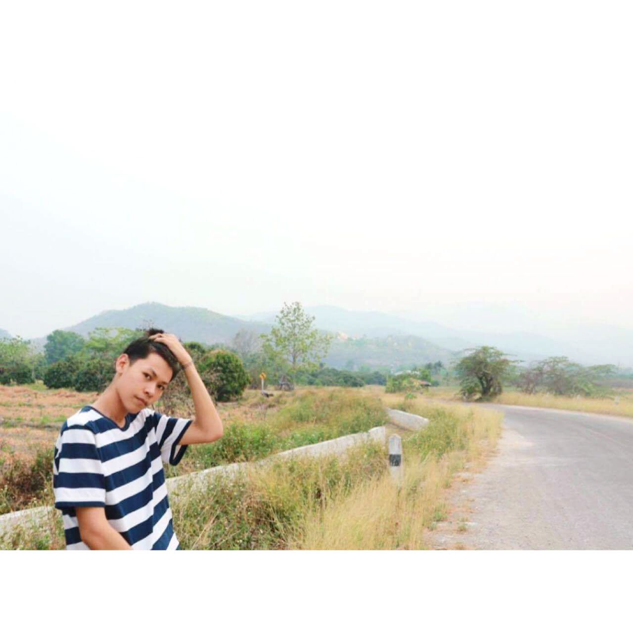 casual clothing, one person, real people, leisure activity, striped, young adult, young women, mountain, outdoors, day, landscape, nature, full length, standing, clear sky, road, happiness, scenics, adventure, lifestyles, beautiful woman, sky, grass, smiling, beauty in nature, tree, adult, people