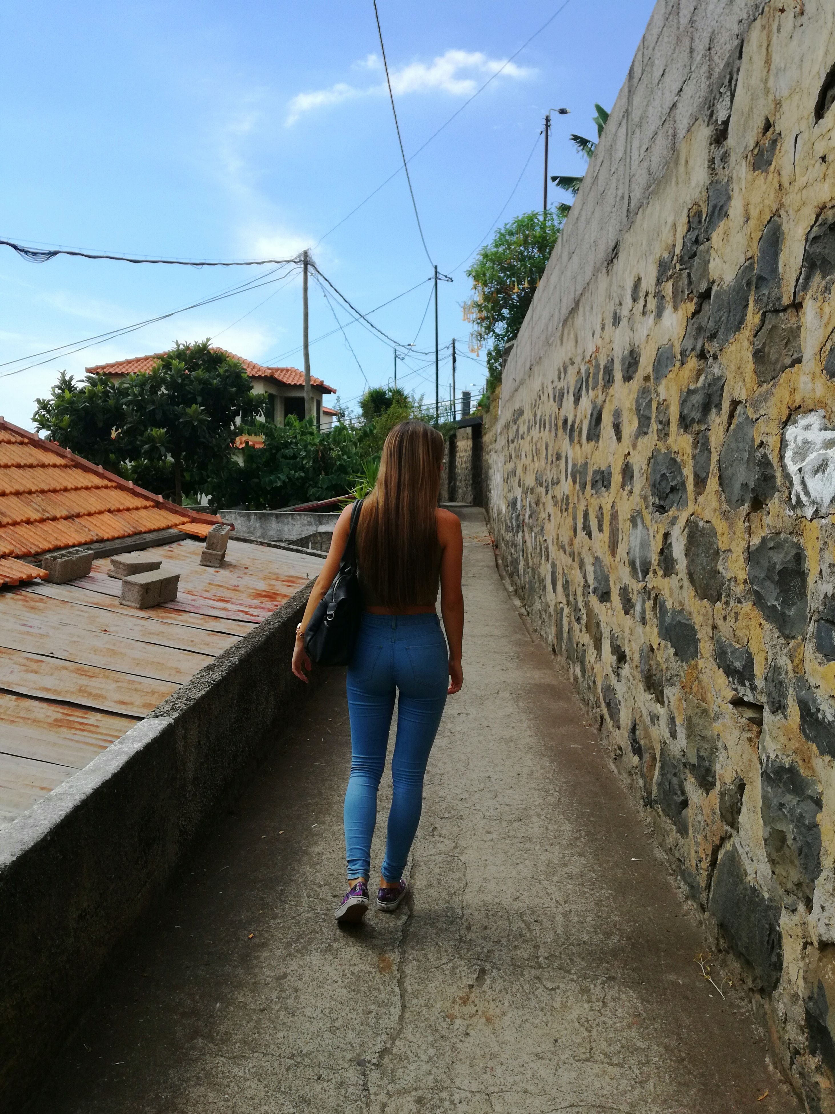 rear view, walking, architecture, built structure, full length, building exterior, casual clothing, cloud, sky, the way forward, day, one woman only, long hair, blue, outdoors, footpath, diminishing perspective