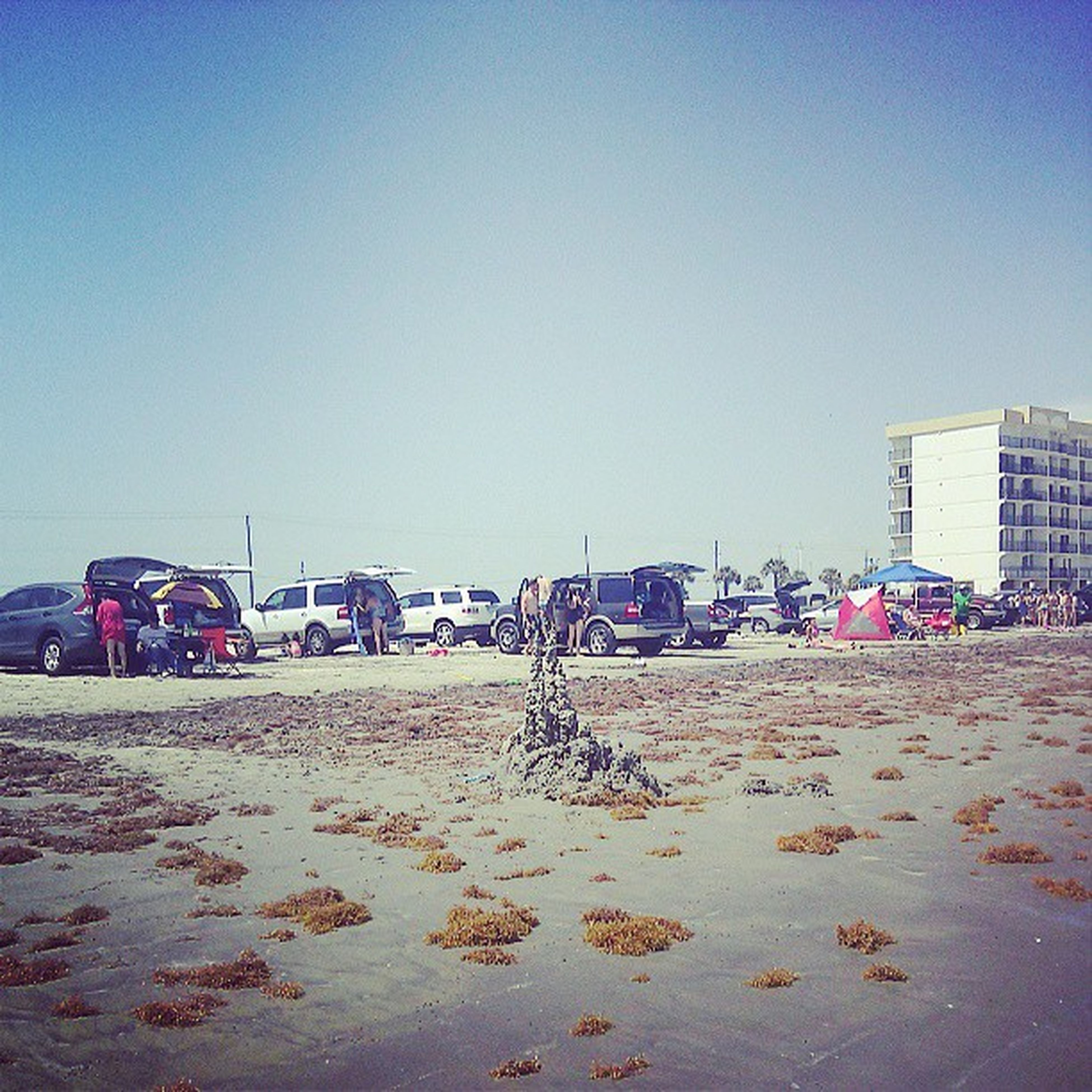 clear sky, beach, copy space, sand, building exterior, built structure, large group of people, architecture, shore, sea, city, incidental people, blue, day, sunlight, outdoors, water, sky, vacations