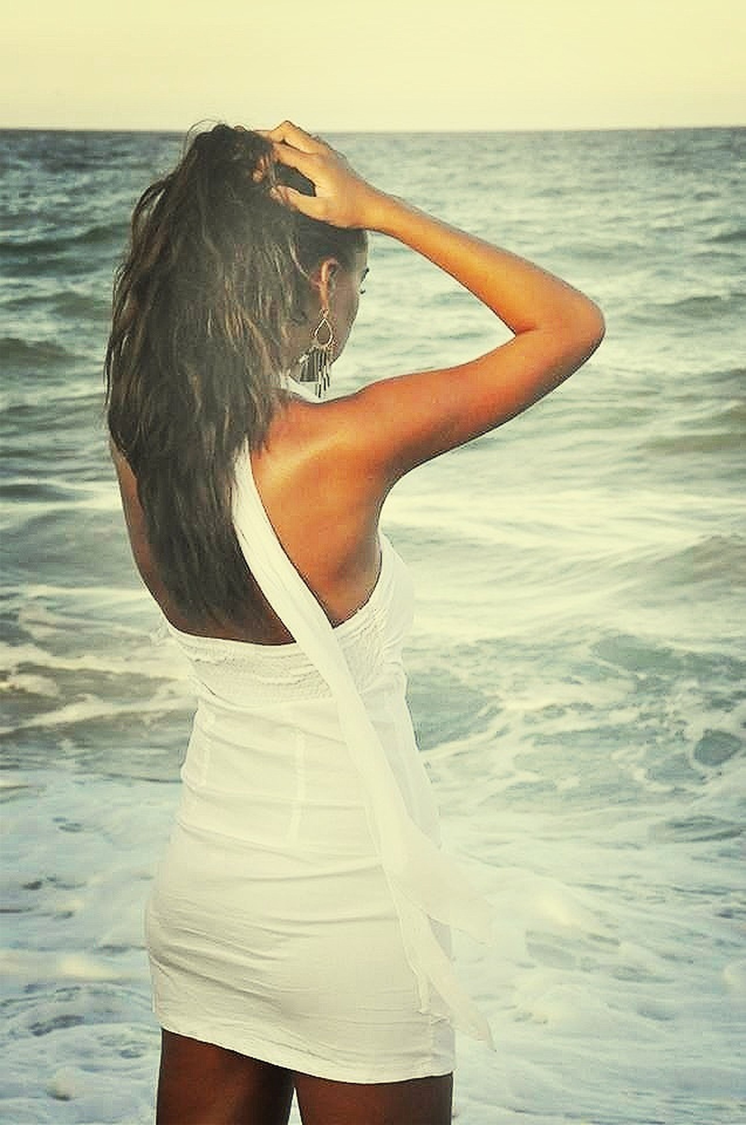 water, sea, rear view, lifestyles, leisure activity, standing, horizon over water, person, three quarter length, side view, nature, young adult, focus on foreground, beauty in nature, waist up, young women, long hair, rippled