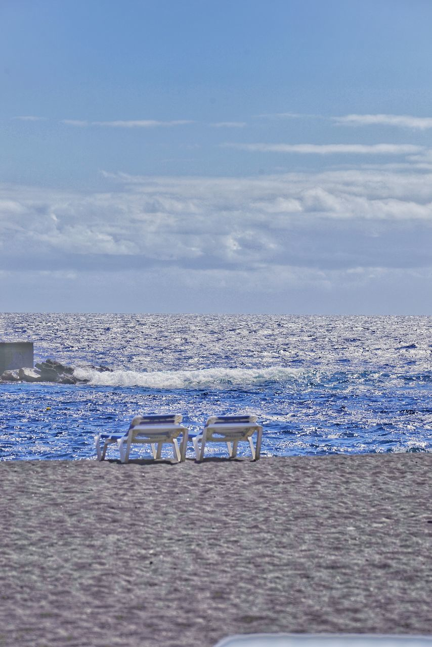 sea, sky, chair, absence, tranquility, empty, nature, blue, no people, scenics, tranquil scene, water, beach, beauty in nature, outdoors, day, horizon over water