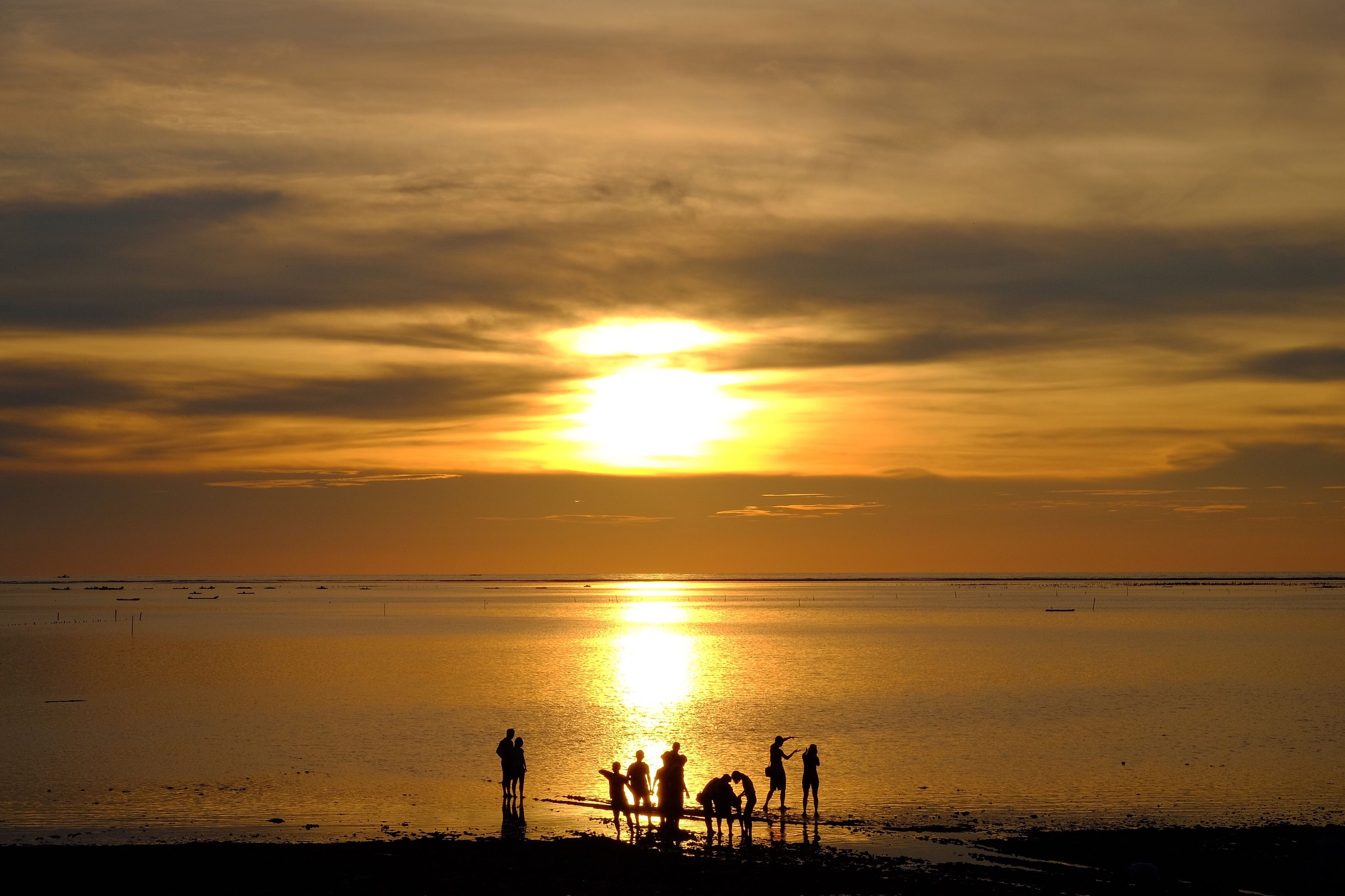 sunset, water, sun, vacations, silhouette, leisure activity, tranquil scene, tourism, scenics, tranquility, lifestyles, medium group of people, tourist, beauty in nature, togetherness, weekend activities, idyllic, enjoyment, childhood, sea, travel, reflection, cloud - sky, orange color, atmosphere, nature, majestic, vibrant color, hobbies, travel destinations