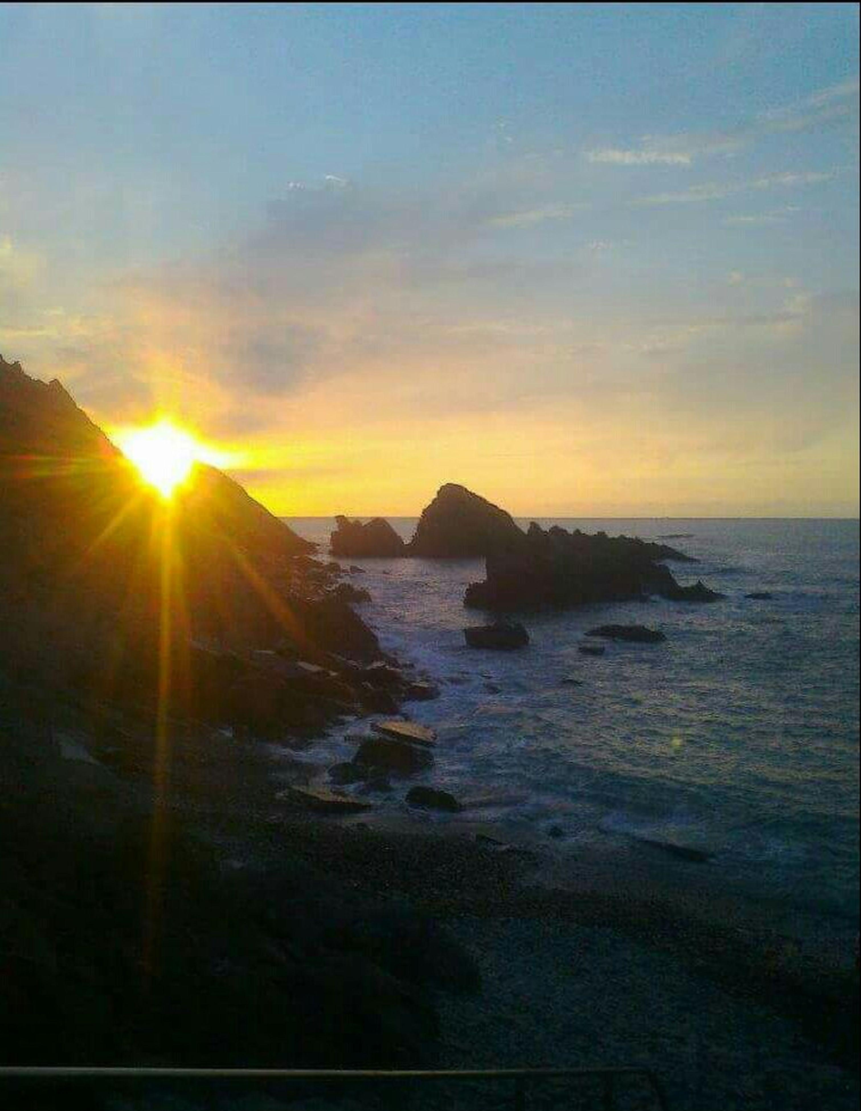 sea, water, sunset, sun, scenics, tranquil scene, horizon over water, beauty in nature, sky, tranquility, beach, sunlight, nature, shore, sunbeam, idyllic, rock - object, wave, reflection, lens flare