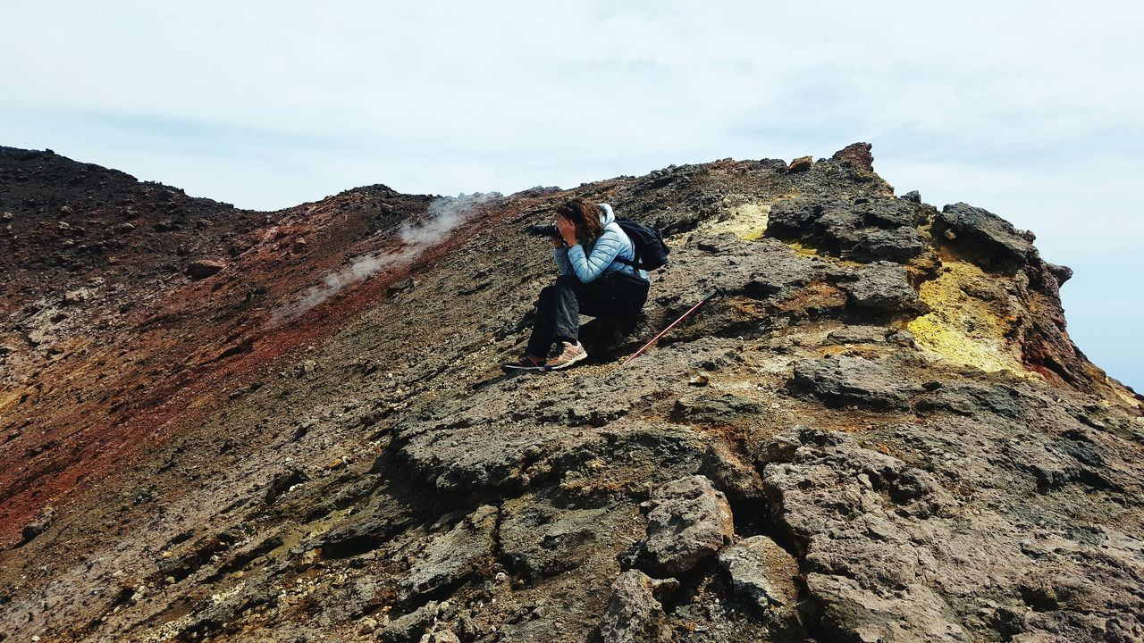 Side View Of Woman Photographing While Sitting On Volcanic Landscape