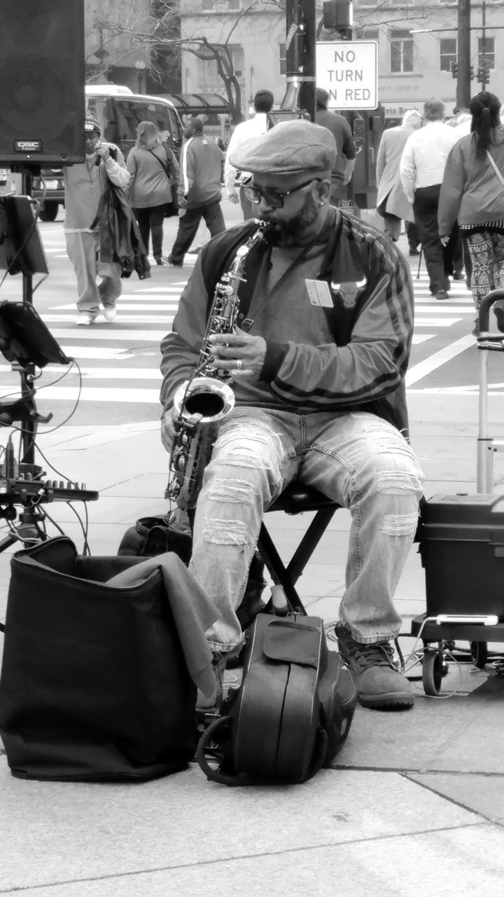 music, musician, real people, musical instrument, men, arts culture and entertainment, playing, sitting, full length, street performer, outdoors, guitar, day, city, crowd, one person, adult, people