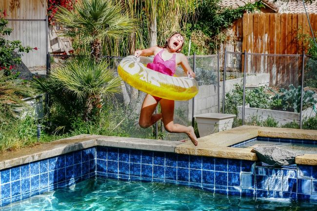 A carefree girl jumping into a blue pool to celebrate the start of summer Blue Child Childhood Day Elementary Age Girl Inner Innocence Jump Laughing Out Loud Leisure Activity Mid-air Outdoor Outdoors Playing Pool Sillouette Sunset Tree Vacation