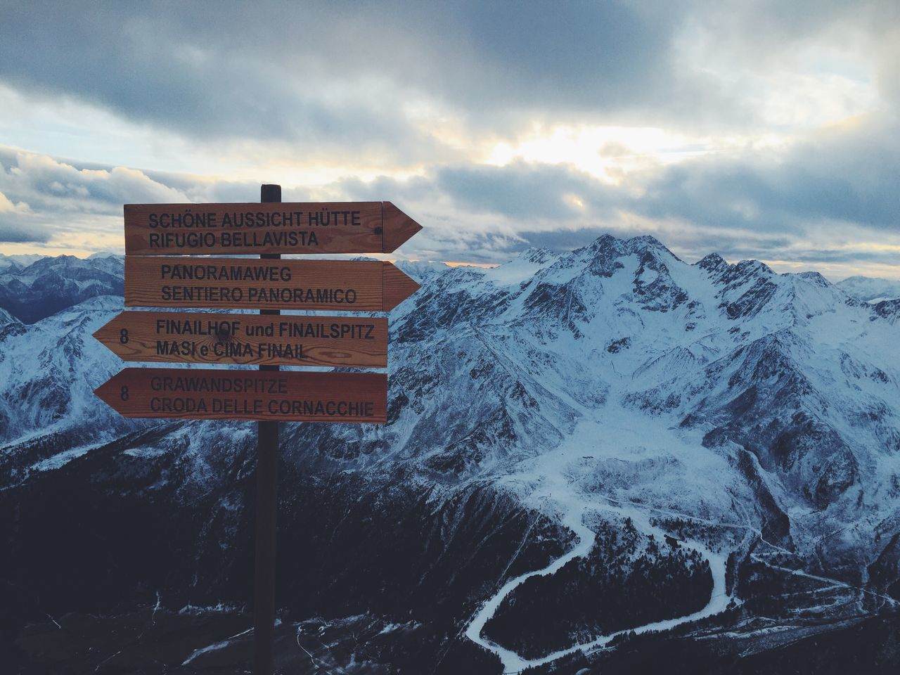 Signboards On Snow Covered Mountains Against Sky