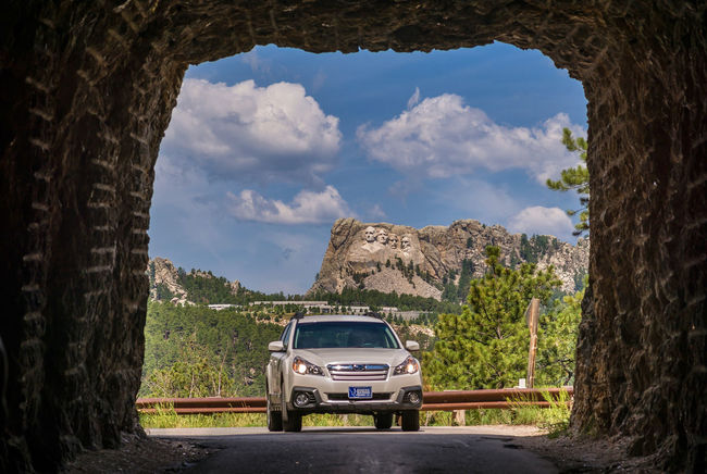 Arch Cloud Cloud - Sky Country Road Custer State Park Day Green Color Land Vehicle Landscape Mode Of Transport Mountain Mt Rushmore Nature No People On The Way Road Scenics Sky The Way Forward Tranquil Scene Tranquility Travel Destinations Tree