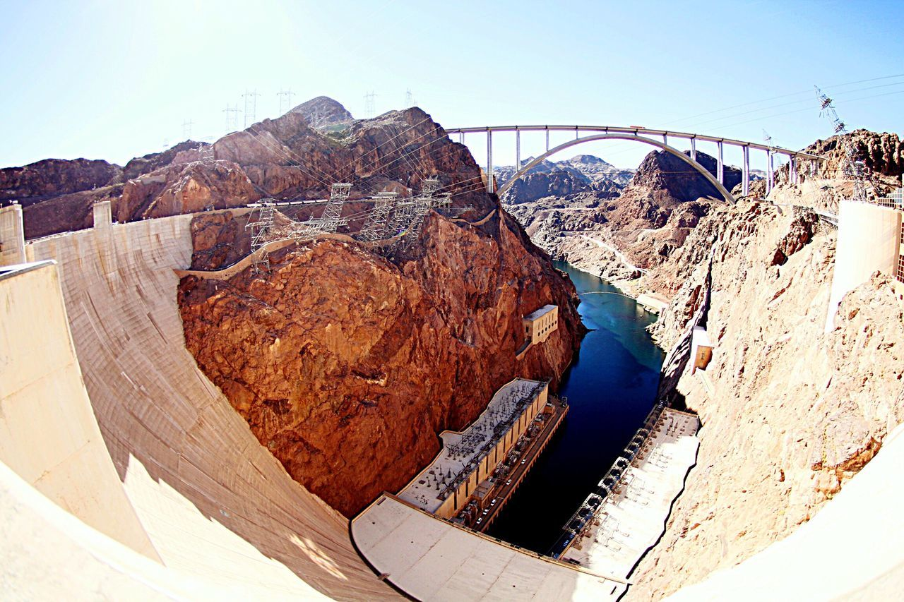 hydroelectric power, dam, engineering, architecture, arch, built structure, day, bridge - man made structure, mountain, fuel and power generation, travel destinations, outdoors, geology, no people, mountain range, physical geography, travel, water, electricity, nature, rocky mountains, clear sky, power station, electricity pylon, landscape, beauty in nature, sky