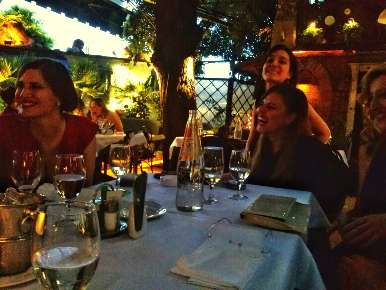 real people, table, sitting, smiling, togetherness, leisure activity, young women, happiness, young adult, outdoors, looking at camera, alcohol, wine, young men, night, two people, portrait, lifestyles, women, wineglass, men, vacations, drink, friendship, people