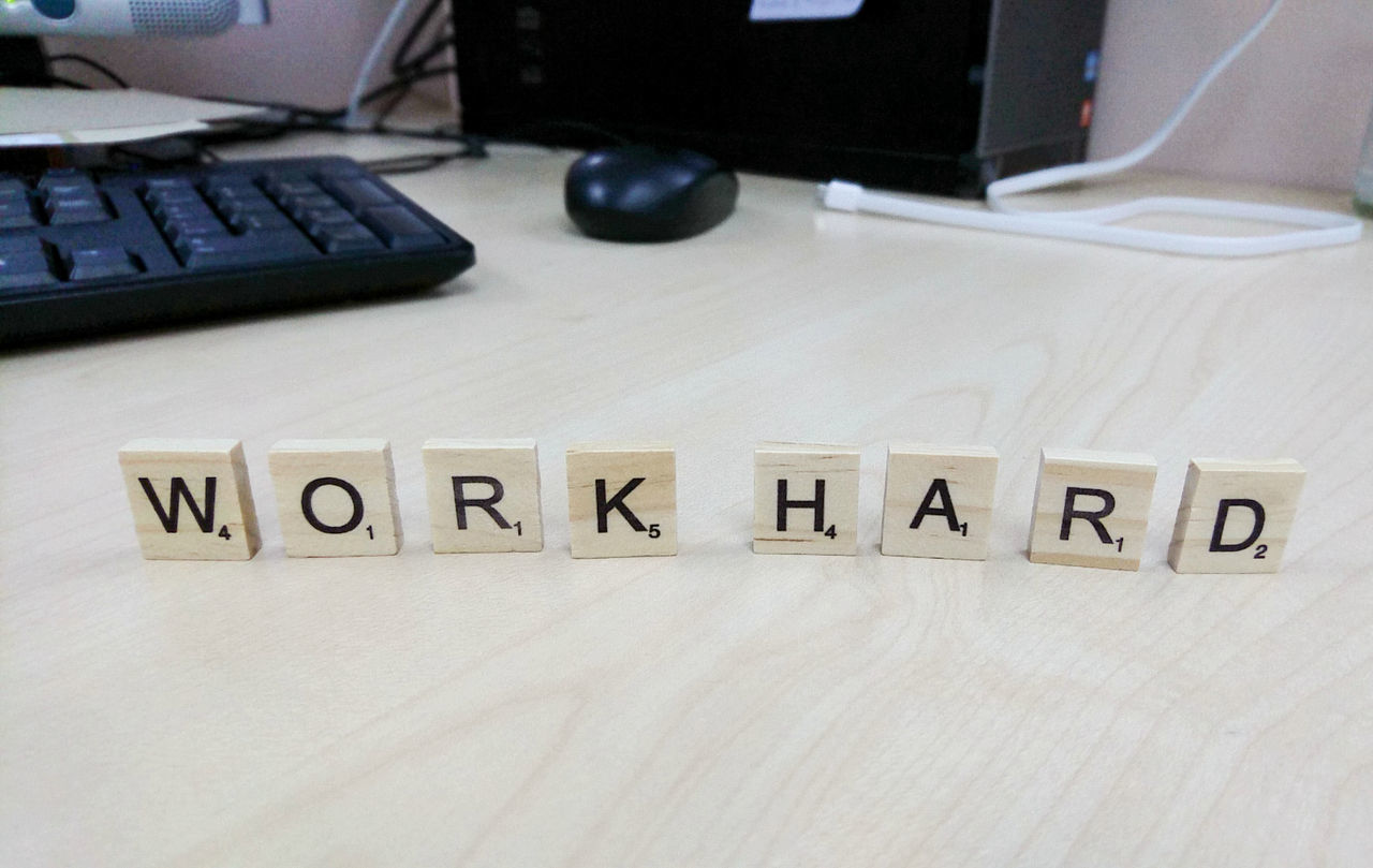 "Scramble wording ""work hard"" on wood table with blurred workplace background Text Communication No People Close-up Alphabet Indoors  Day Work Hard Working Workplace Business Finance Game Scrambled Text Background Marketing Wording"