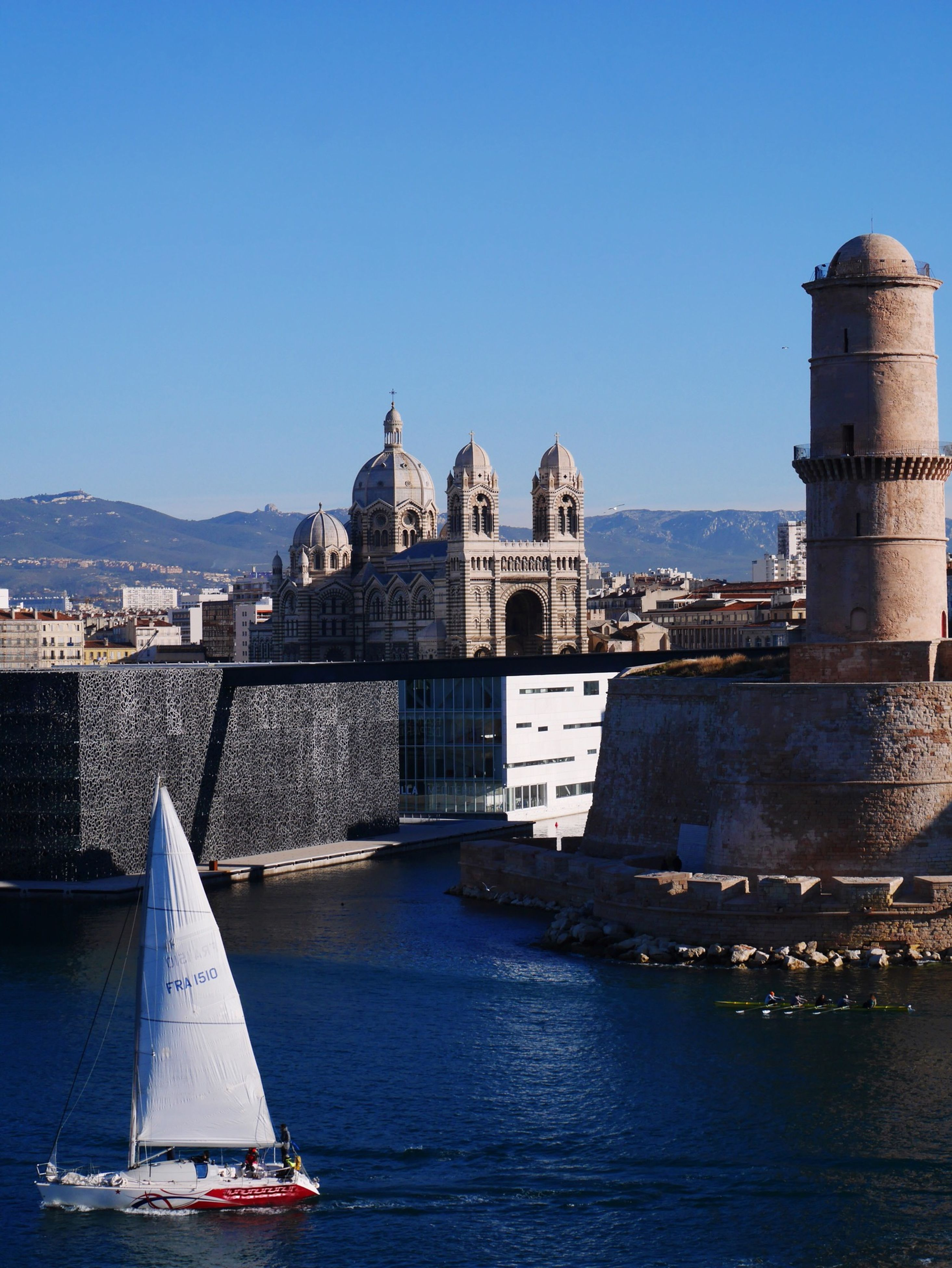 Sailboat Sailing By Marseille Cathedral Against Clear Blue Sky