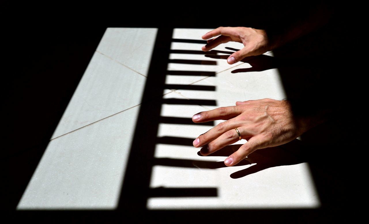 Hand playing the light and shadow piano Adult Adults Only human body part human hand indoors light and shadow Music musical instrument one person people Piano pink color Sound Piano Moments
