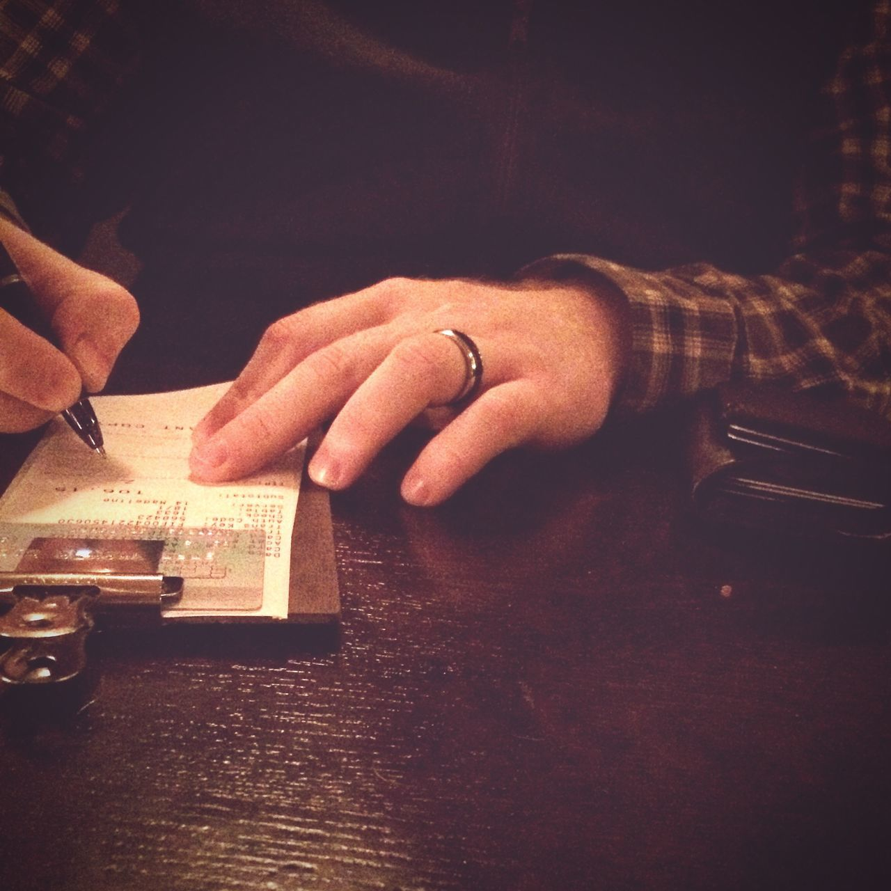 Cropped Hand Signing Credit Card Bill On Table At Restaurant