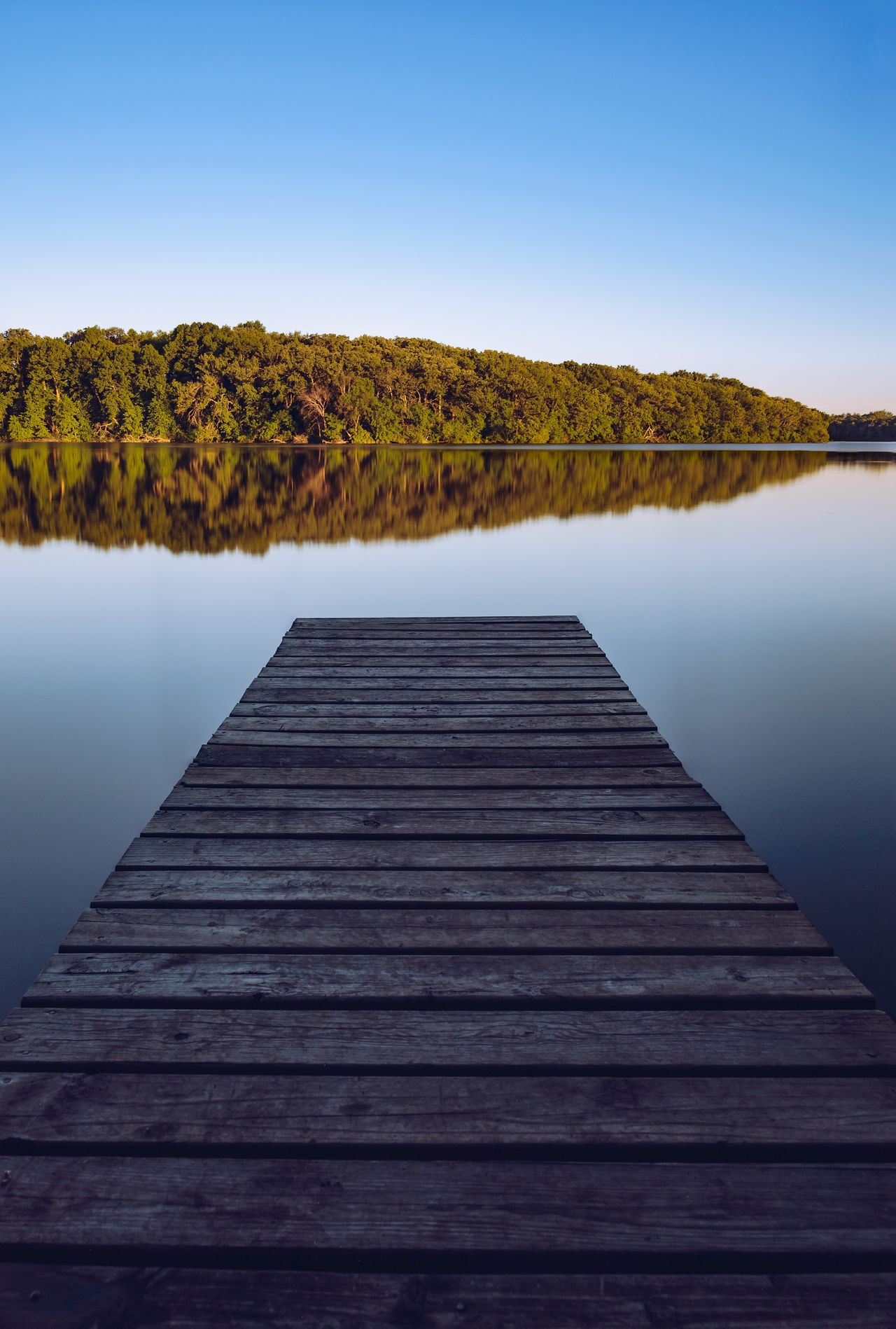 Reflections on the Lake Water Lake Tranquil Scene Nature Scenics Beauty In Nature Pier Clear Sky Tranquility No People Outdoors Wood - Material The Way Forward Day Jetty Blue Sky Wood Paneling Tree Reflection Reflections Reflect Boat Dock Dock